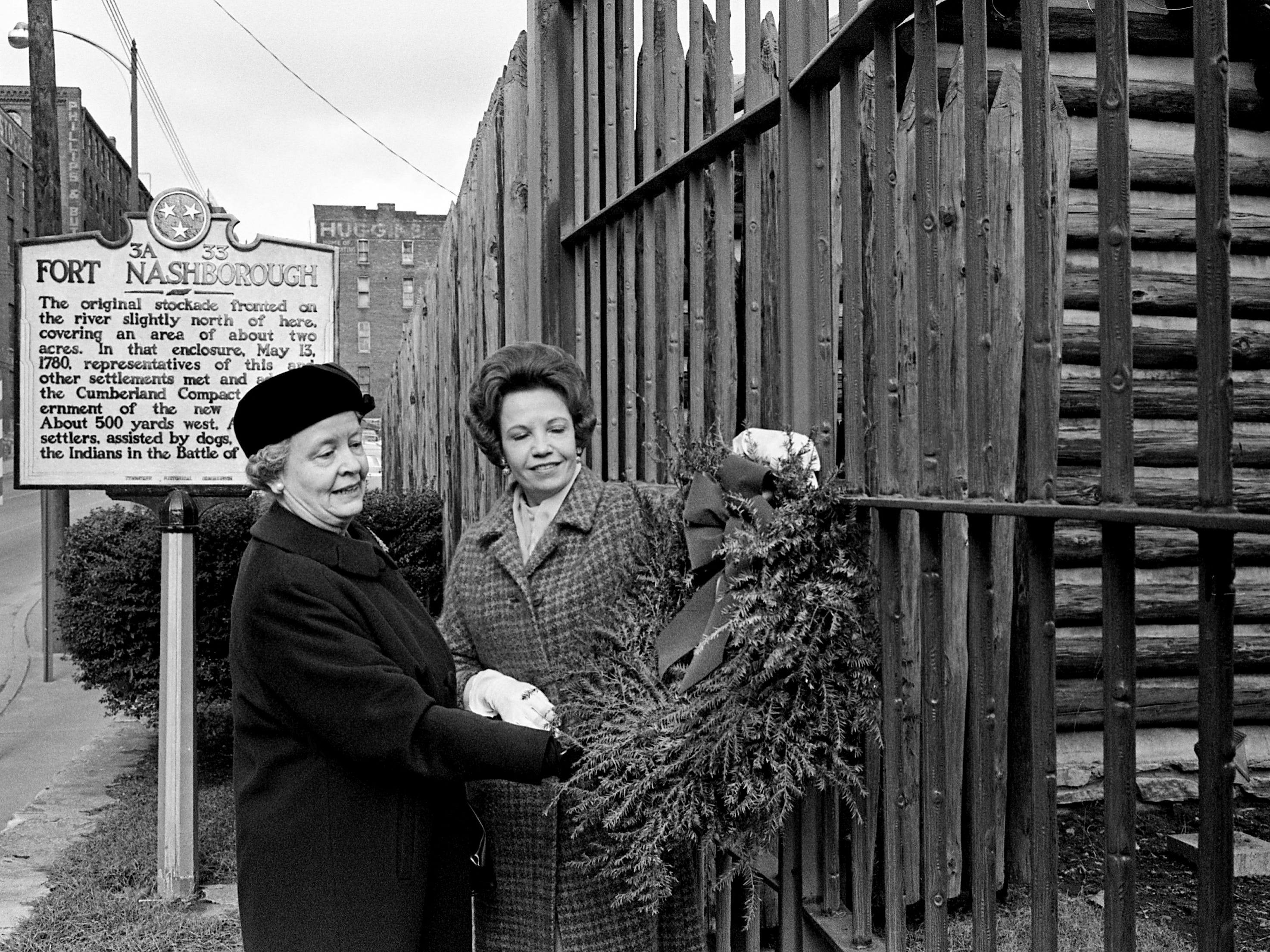 For years, members of the Belle Meade Chapter, DAR, have placed a Christmas wreath on the gates of Fort Nashborough in downtown Nashville. Hanging the wreath this year on Dec. 14, 1968 are Miss Madeline Knight, left, and Mrs. Jean Lakoff.