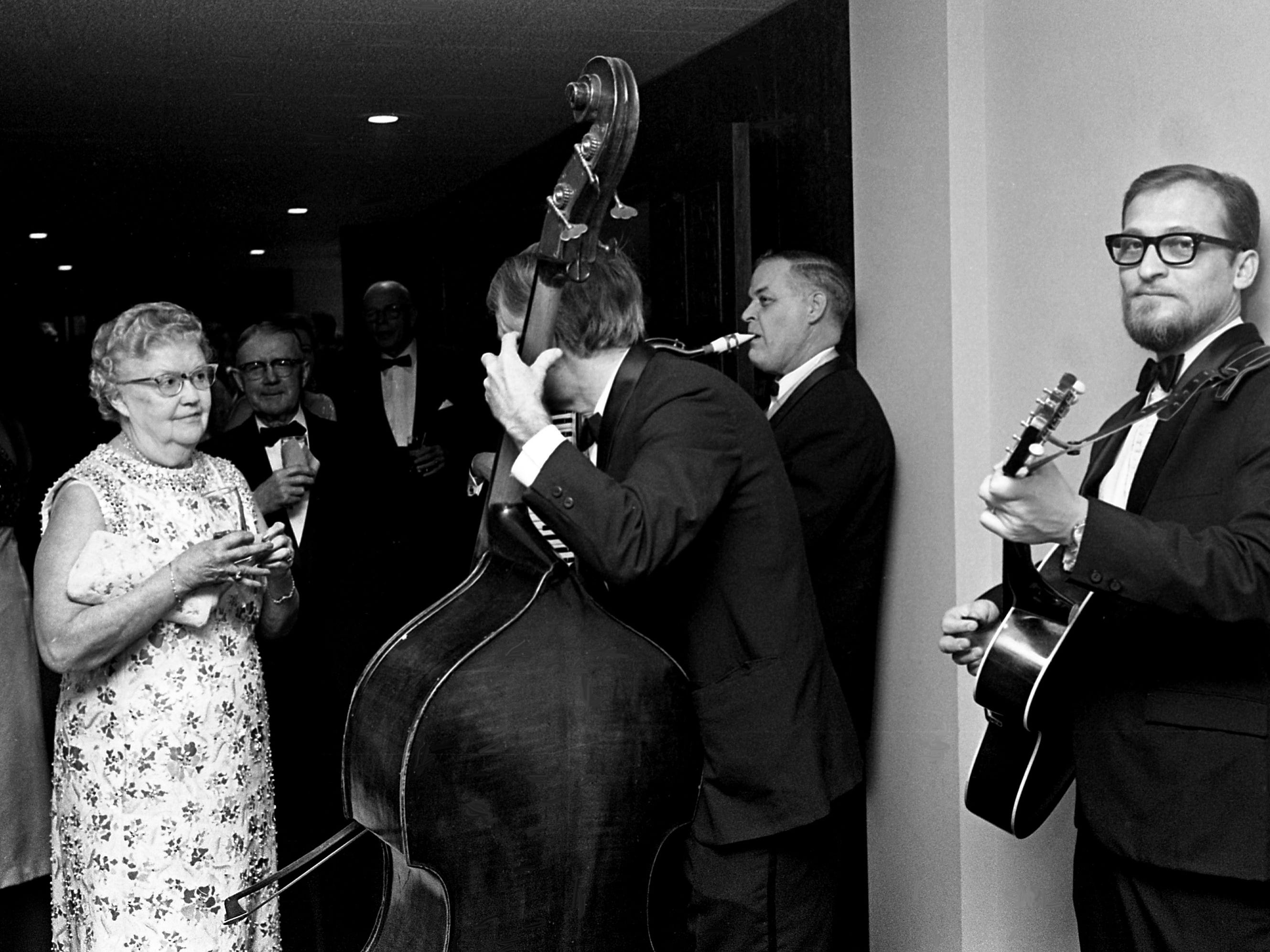 With music furnished by Sam Hollingsworth, Mrs. John Youmans, left, breaks into her own impromptu finger-snapping jig during the informal hour of the new Sheraton-Nashville's Opening Ball on Dec. 13, 1968.