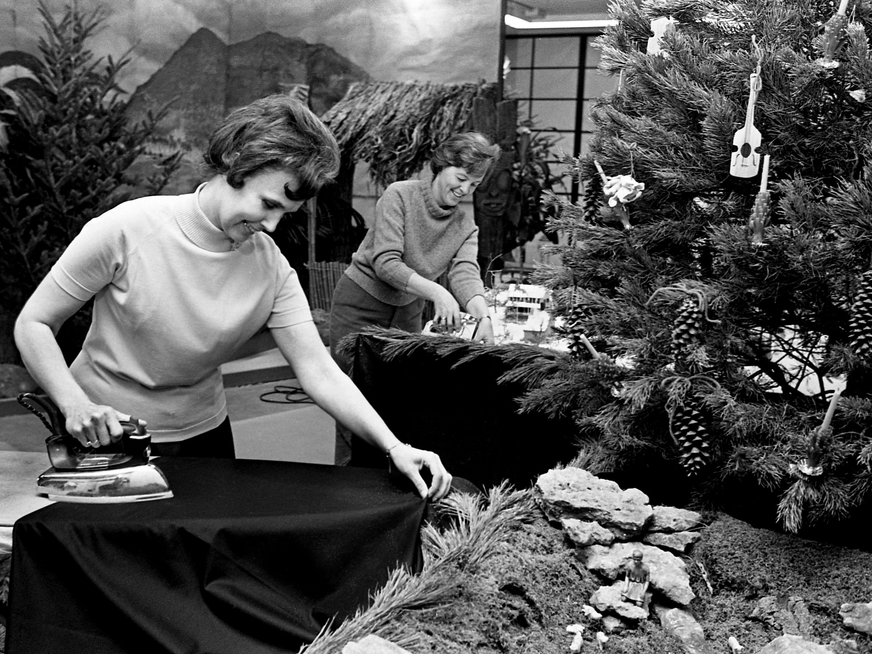 Irons and staplers were busy all week as members of more than 75 garden clubs were working on the 21 trees from many lands and seven exhibits for the upcoming 4th annual Christmas at Cheekwood event. Ironing material for the skirts of the Fleur de Lis Garden Club exhibit Dec. 3, 1968 is Mrs. Lem Tanksley, left, and stapling is Mrs. O.D. Glaus.