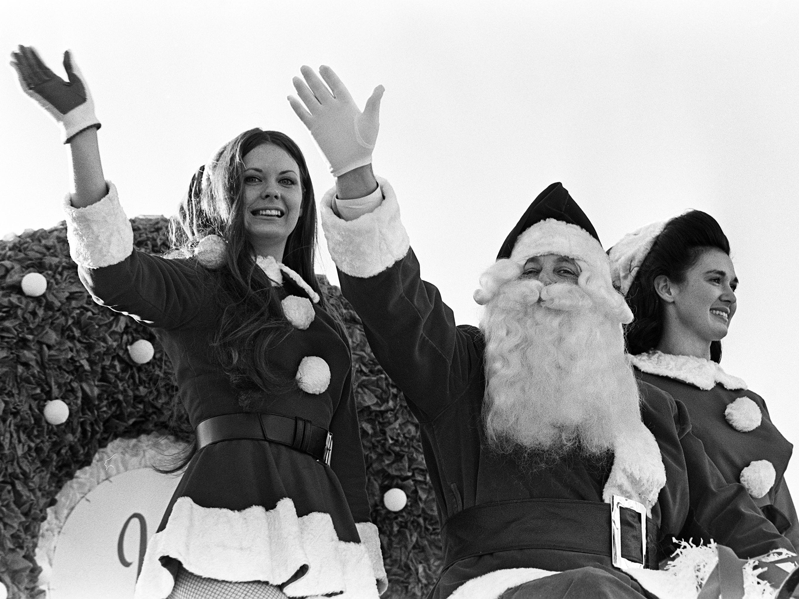 Santa Claus, the traditional favorite, and his two helpers, wave season's greetings to some of the estimated crowd of 125,000 at the 16th annual Nashville Christmas parade Dec. 8, 1968.