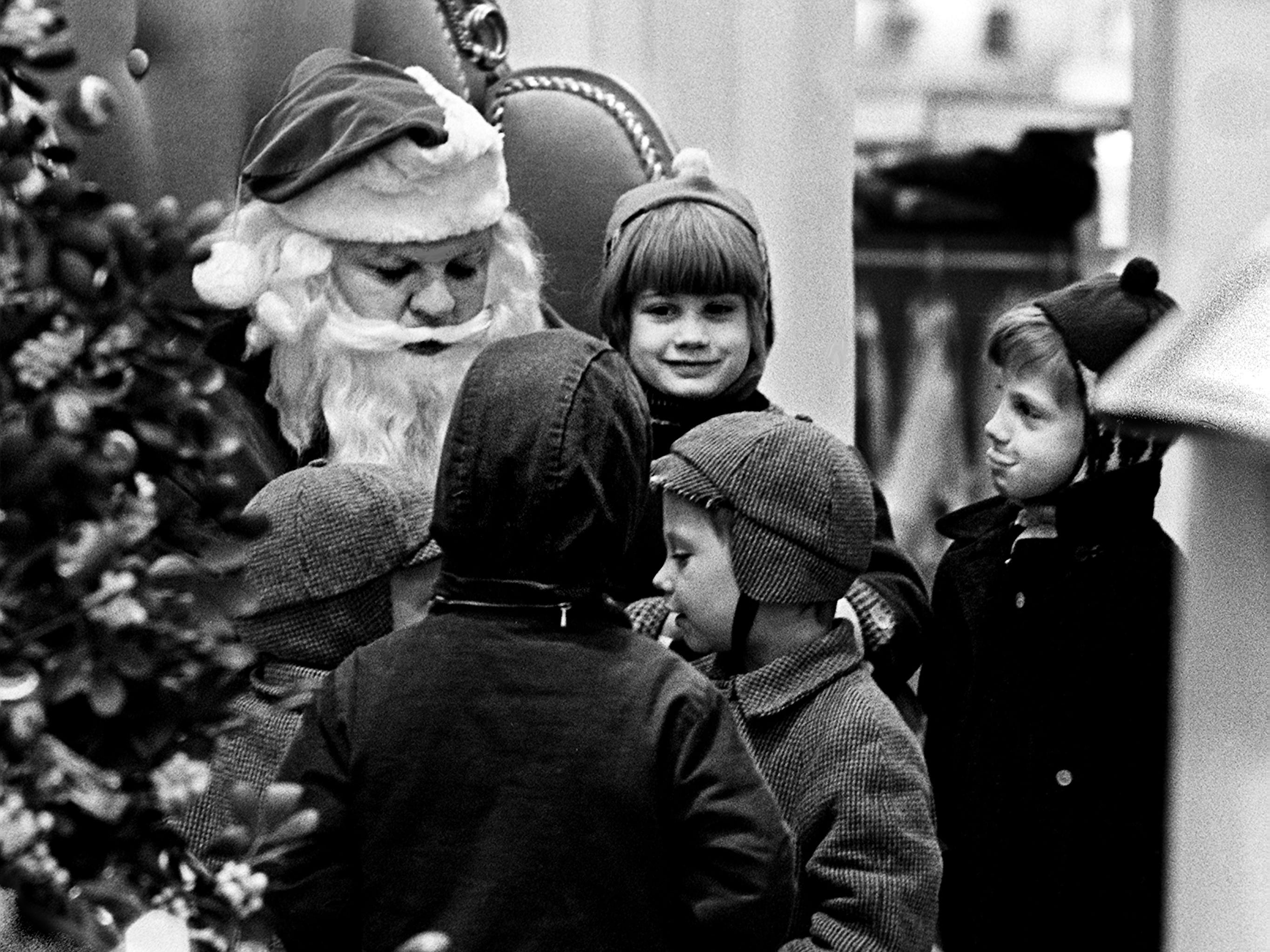 Seven-year-old Cynthia Anderson, center, daughter of Mrs. Lacie Anderson of Berry Street, sits on the lap of Santa Claus as other kids wait their turn at a downtown Nashville department store Dec. 7, 1968.