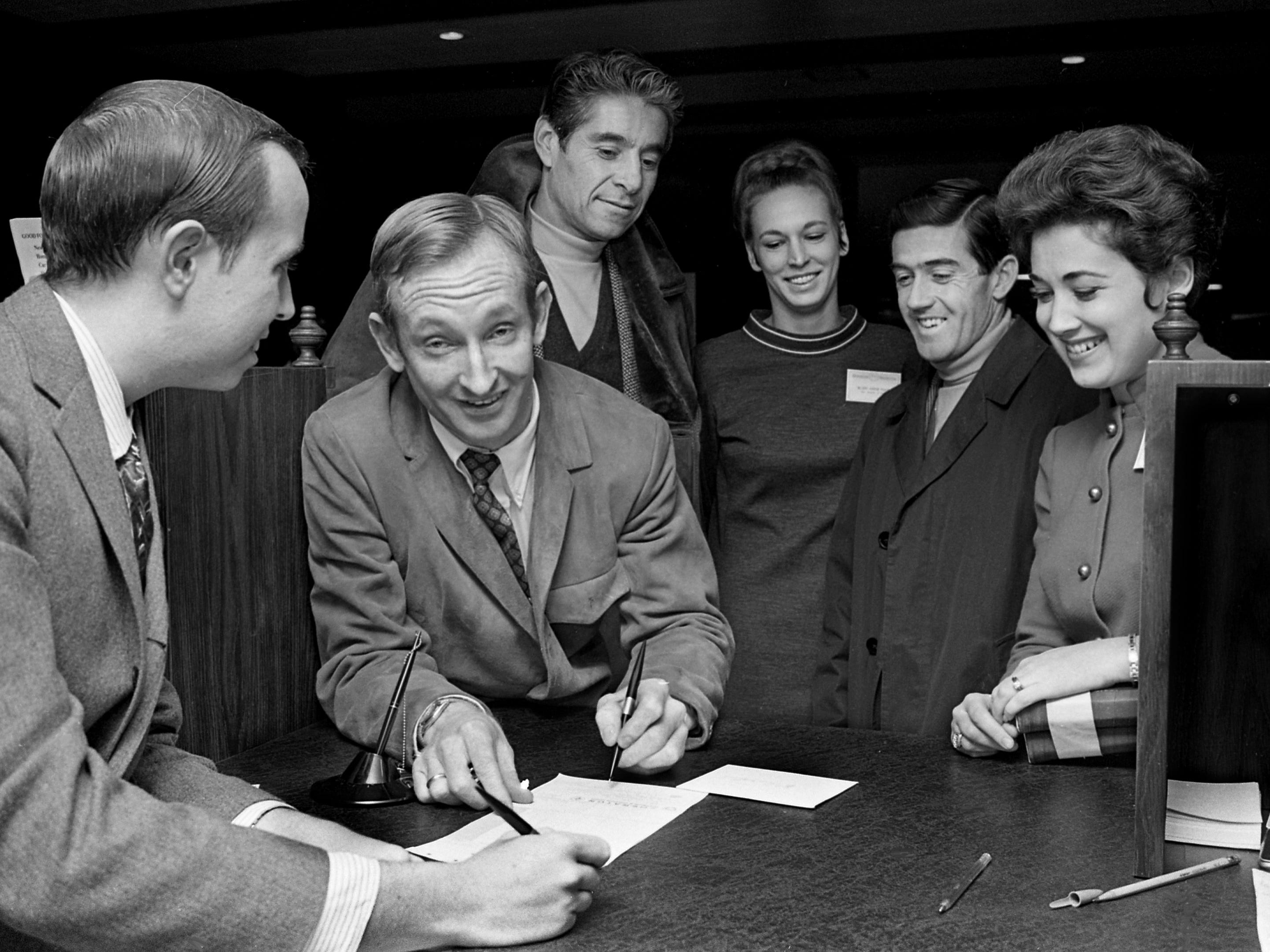 Host David Stone, left, helps Rod Laver, the world's top-ranked tennis player, to sign in at the new Sheraton Motor Inn on Dec. 5, 1968, while players Pancho Gonzales and Ken Rosewall, second from right, wait their turn as hostesses Ellen Tune, third from right, and Carolyn Wallace, right, look on. They were in Nashville for the Dixie Tennis Classic indoor championship at Vanderbilt's Memorial Gym.