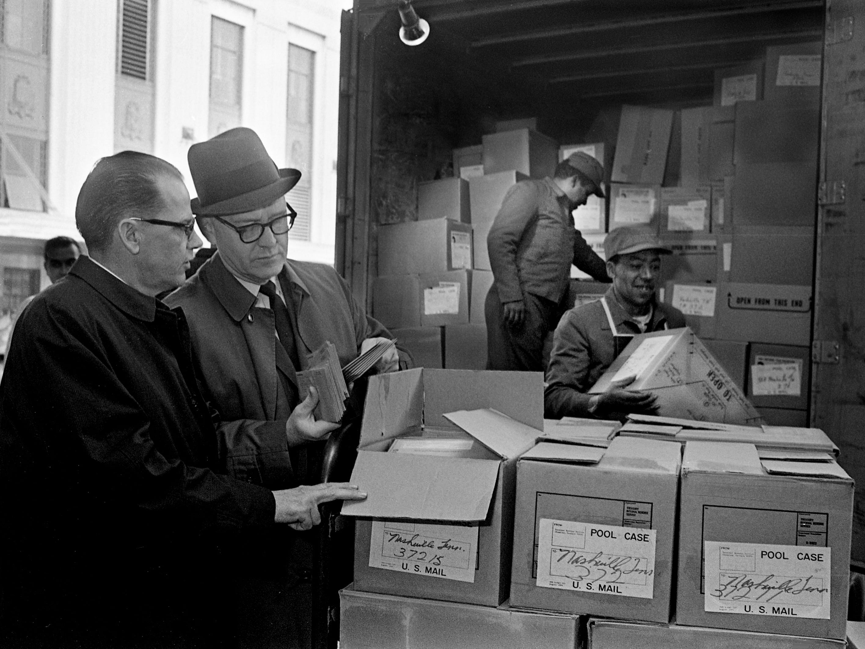 Assistant Postmaster Frank Jarrell, left, and IRS district director James A. O'Hara examine boxed 1968 income tax forms being unloaded by workers at the downtown U.S. post office Dec. 27, 1968. The IRS will send out 1.3 million forms to residents of Tennessee.