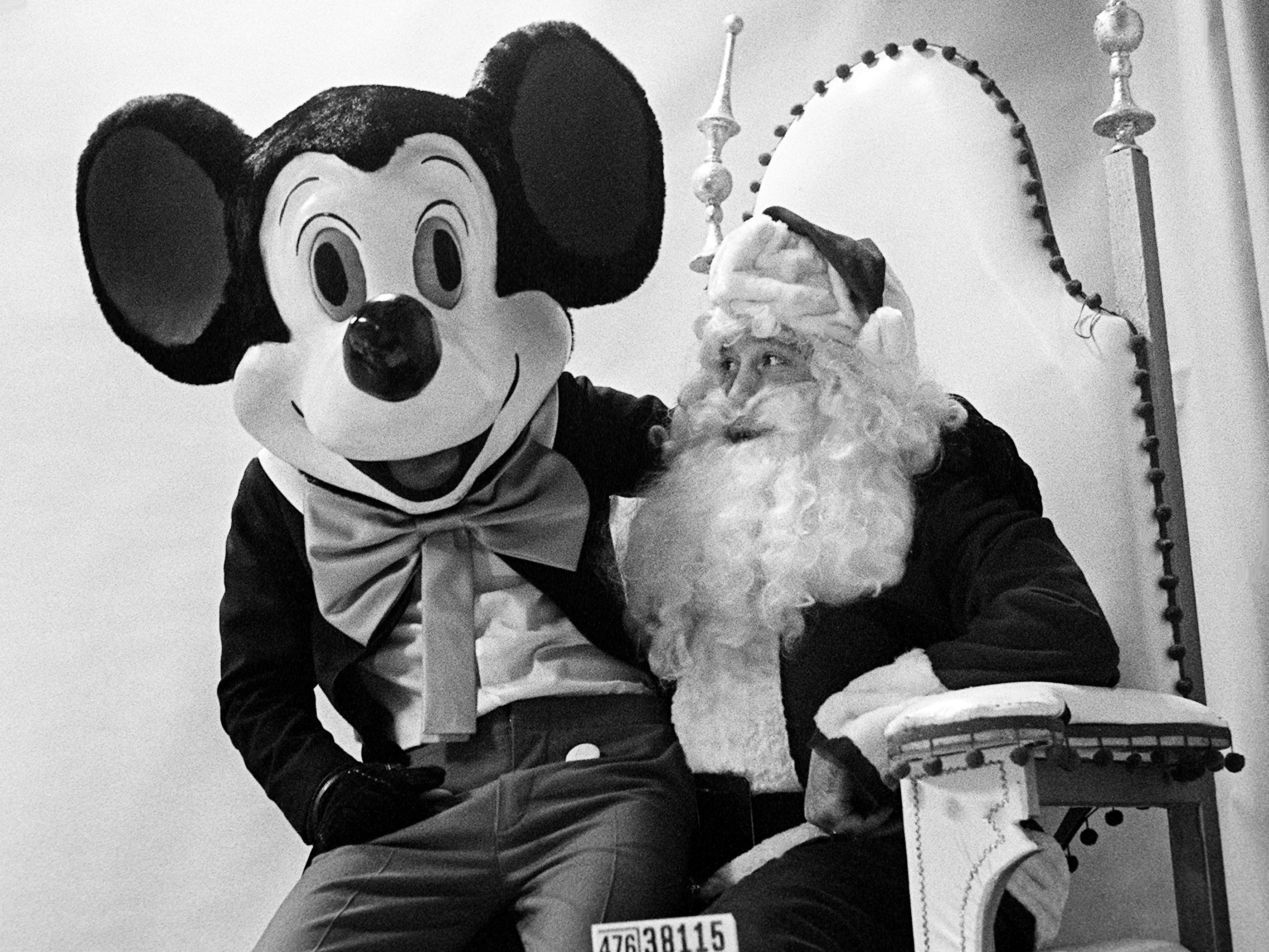 Mickey Mouse takes a break to let Santa know whats he want for Christmas at Harveys Dec. 16, 1968. The popular Disney cartoon character, along with Pluto, greet young and old shoppers each day in the store.