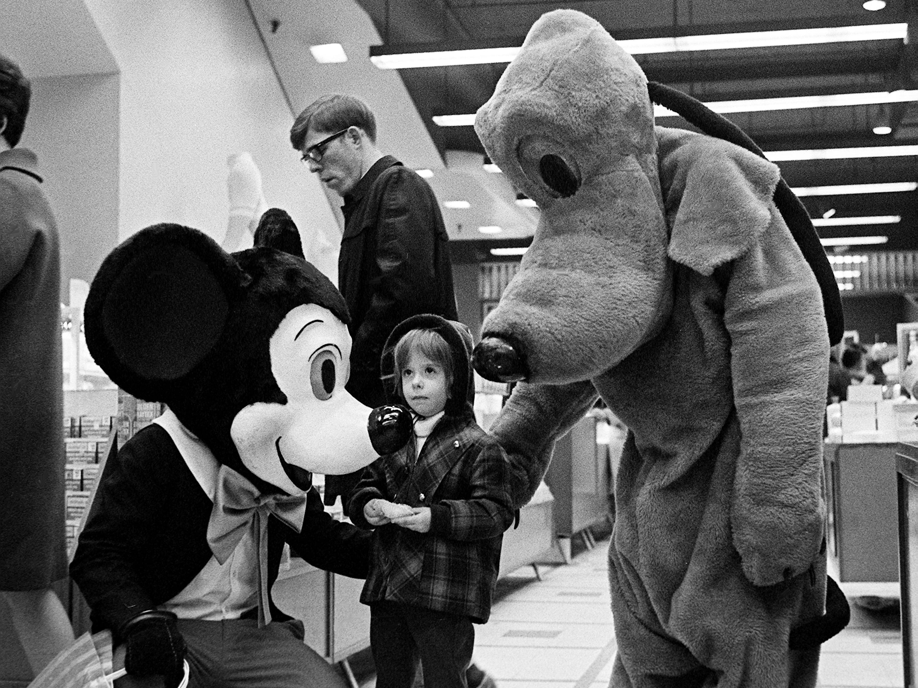 Tiny Nicole Jelesoff, 4, stares in amazement as she is confronted by Mickey Mouse and Pluto at Harveys in downtown Nashville on Dec. 16, 1968. The popular Disney cartoon characters, brought to life by Glenn Gailbreath, 18, and Junior Warren, 17, greet young and old shoppers each day in the store.
