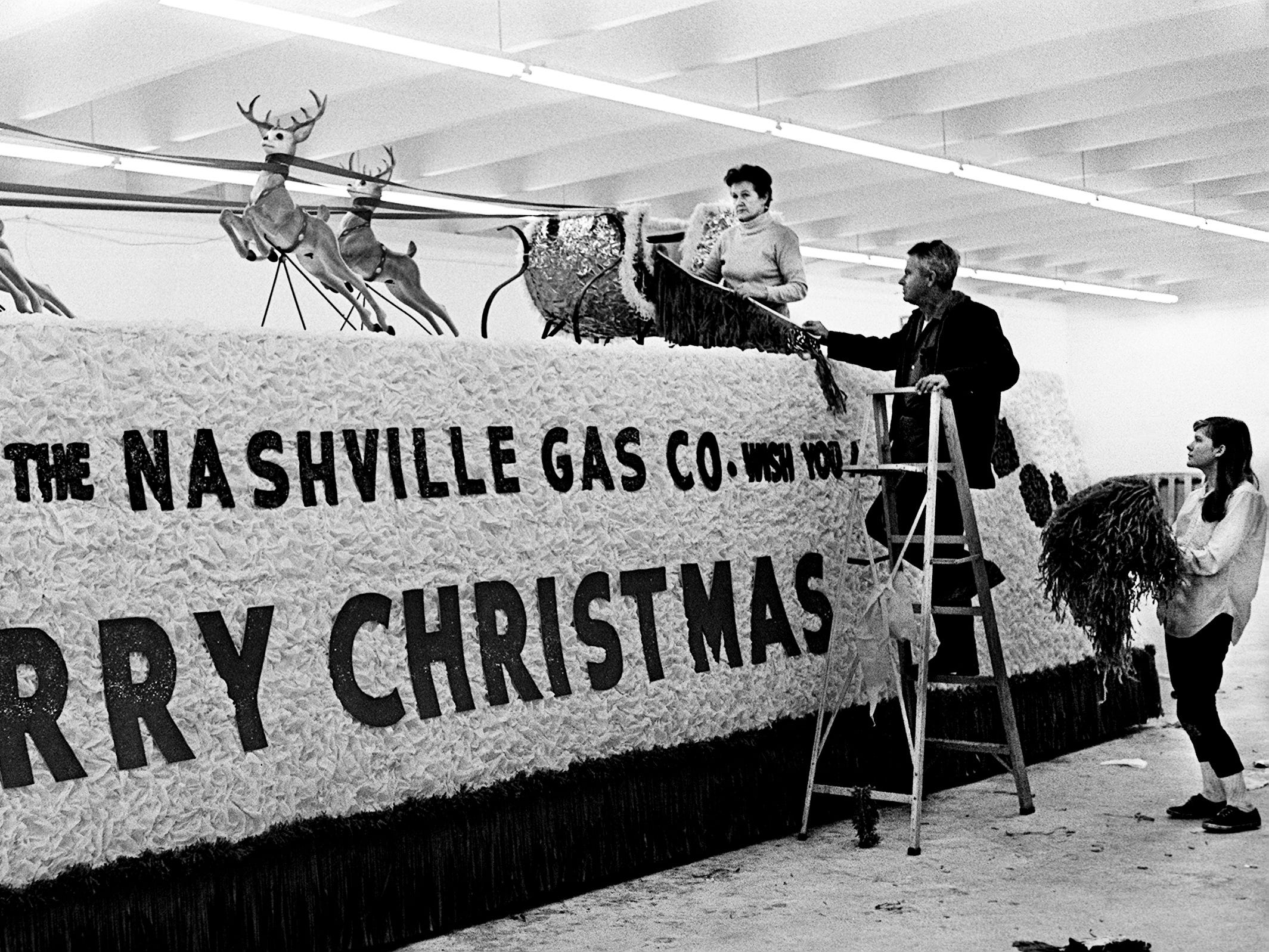 Santa Claus will ride atop this float when the Nashville Area Chamber of Commerce and the Nashville Gas Co. co-sponsor the 16th edition of the Nashville Christmas Parade. On the ladder at the fairgrounds Dec. 5, 1968, is Paul Stalls of Clarksville, a professional parade decorator. His assistants are Martha Utermarck, left, and Mary Ann Kennon, both of Clarksville.