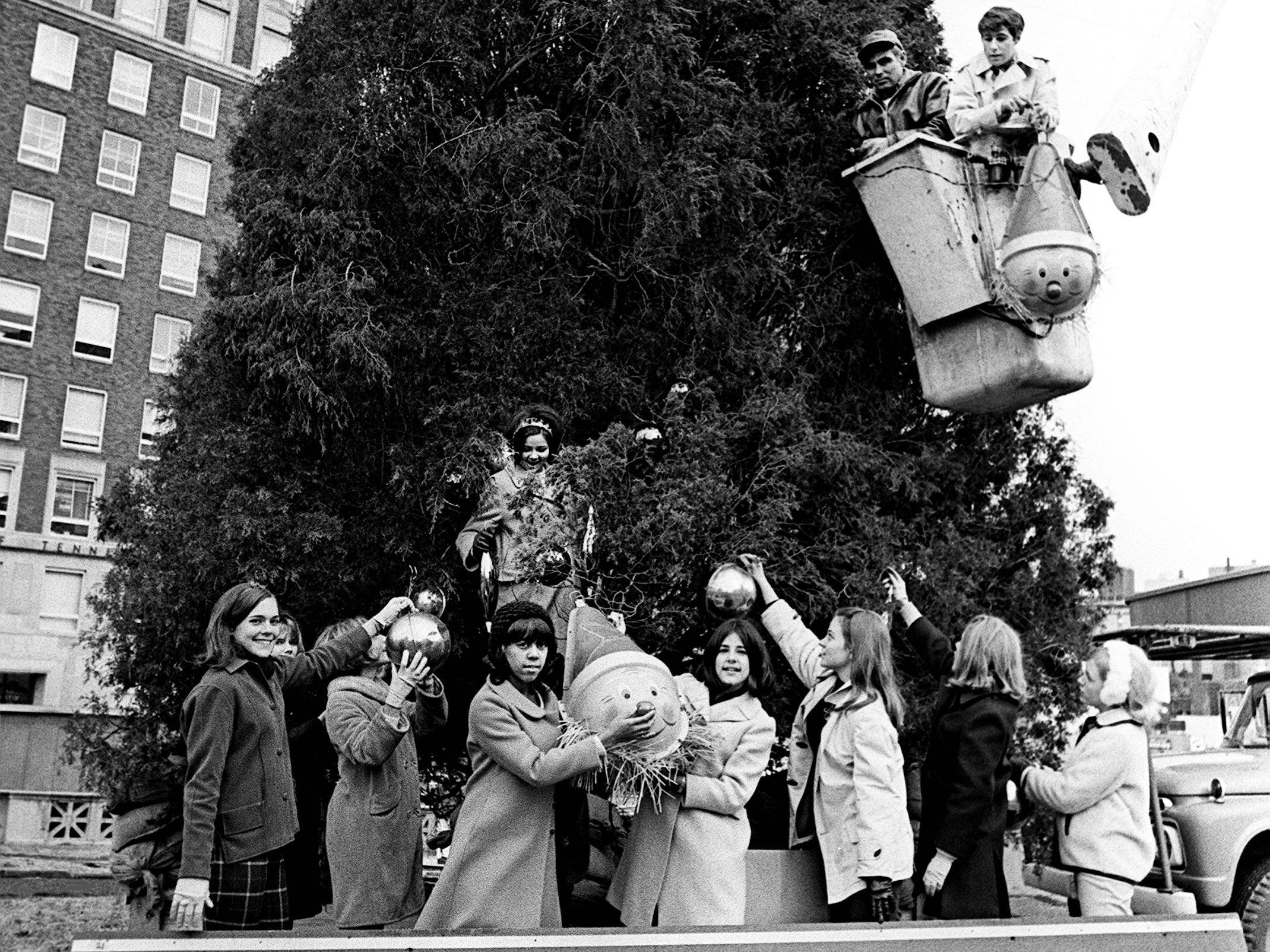 Members of Castner Knott's Teen Board help decorate Nashville's Christmas tree in Memorial Square Nov. 19, 1968 as Don Little, above right, Overton High senior and president of the Teen Board, oversees from a giant hoist. The tree is being prepared for the upcoming lighting ceremony.