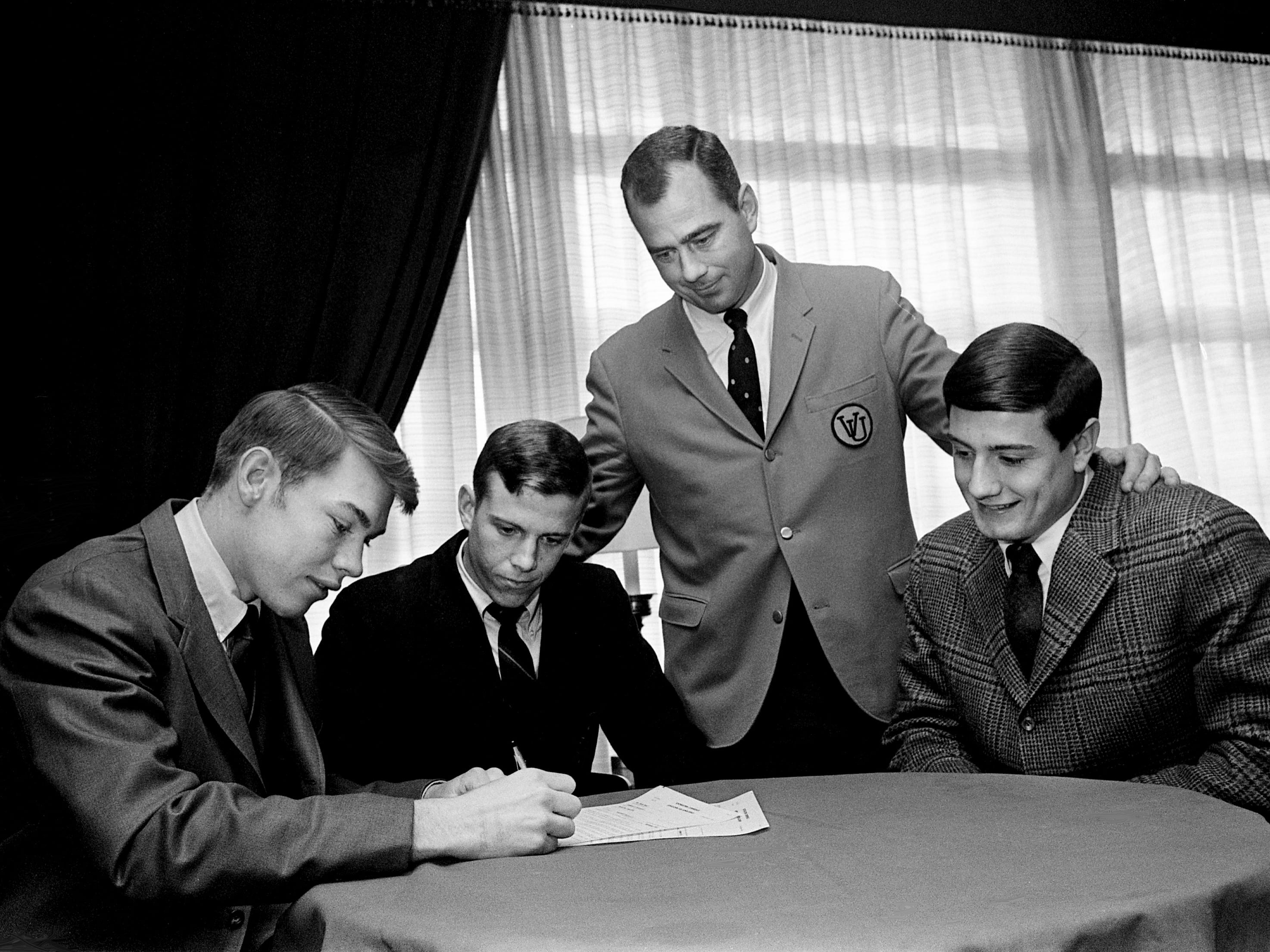 "Vanderbilt head football coach Bill Pace, standing, looks on as MBA All-Metro linebacker Barrett Sutton signs a grant with Vanderbilt at Hillwood Country Club on Dec. 14, 1968. Looking on are future teammates Ken ""Stoney"" Stone, second from left, of Columbia Military Academy and All-Metro tackle Gino Marchetti of Father Ryan, both of whom also signed."