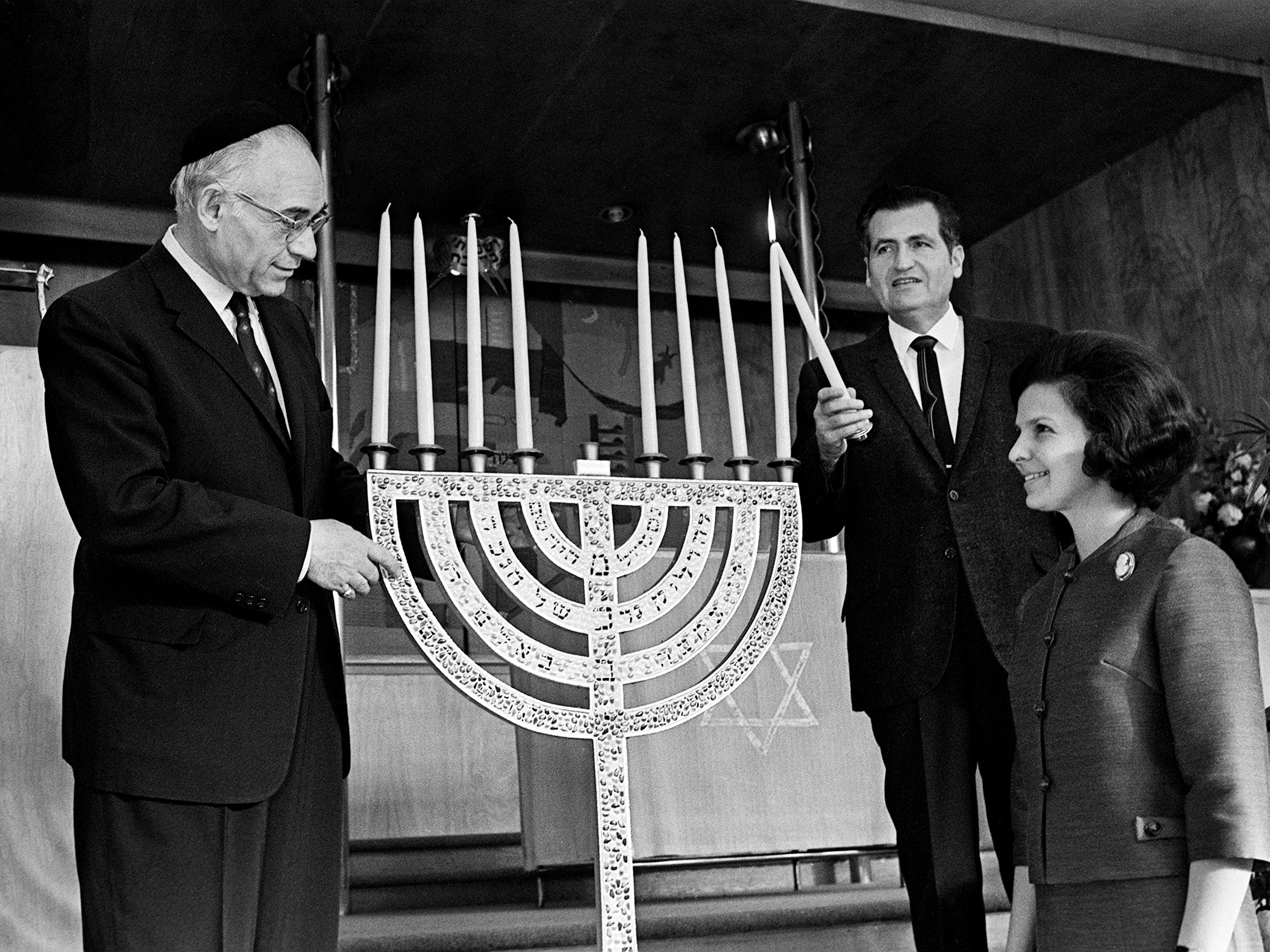 Cantor Bernard Glusman, left, of the West End Synagogue, checks the Menorah that he constructed while Rabbi Jerome Kestenbaum, center, checks the candles Dec. 11, 1968, for the upcoming Hanukkah. Assisting in the final check is Mrs. Leonard Seloff, president of the West End Sisterhood.