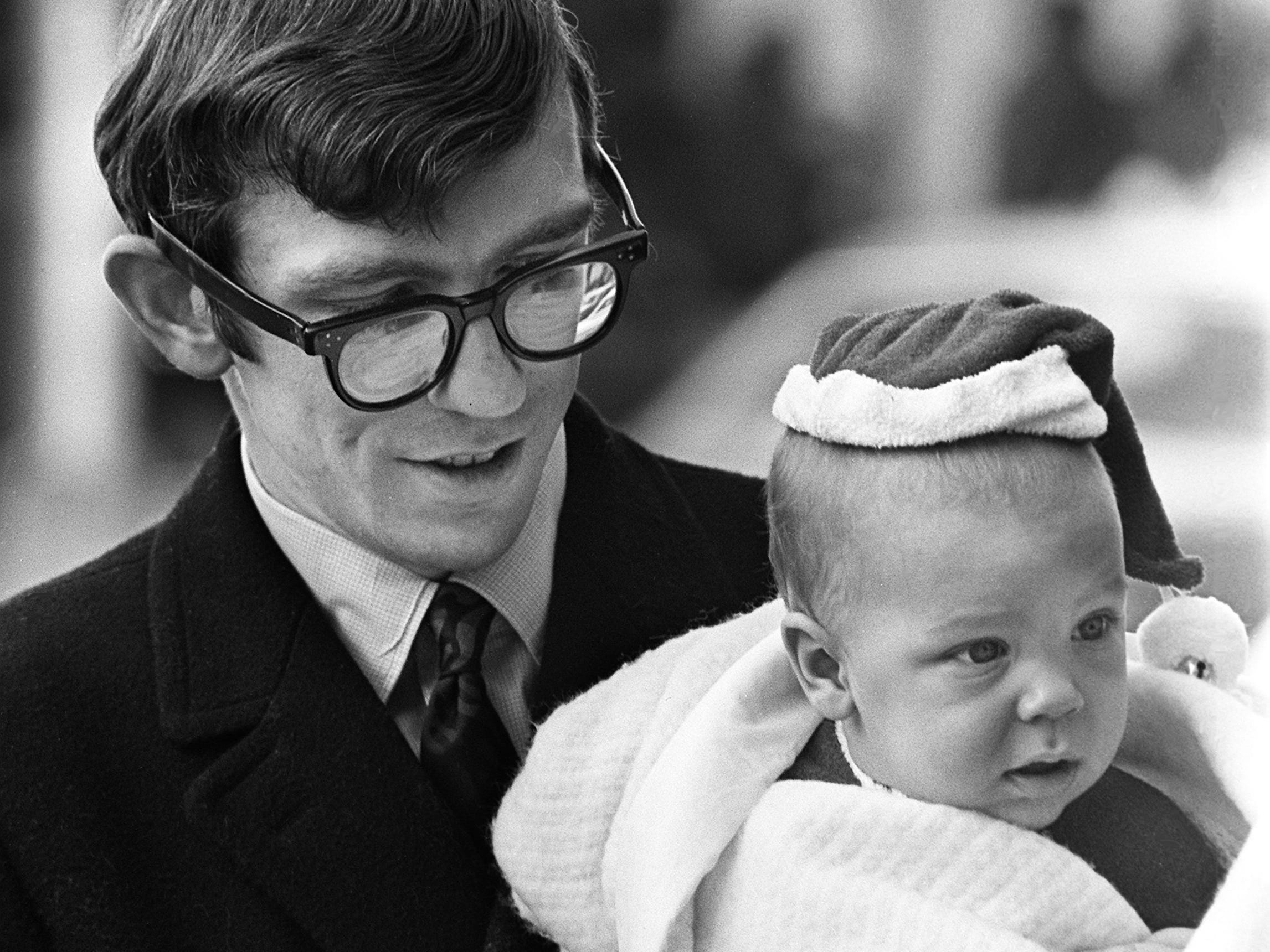 Christopher Willy, six months old, appears not too happy about all this business of Christmas shopping as he accompanies by his father, David Willy of Nashville, on a trip downtown Nov. 30, 1968.