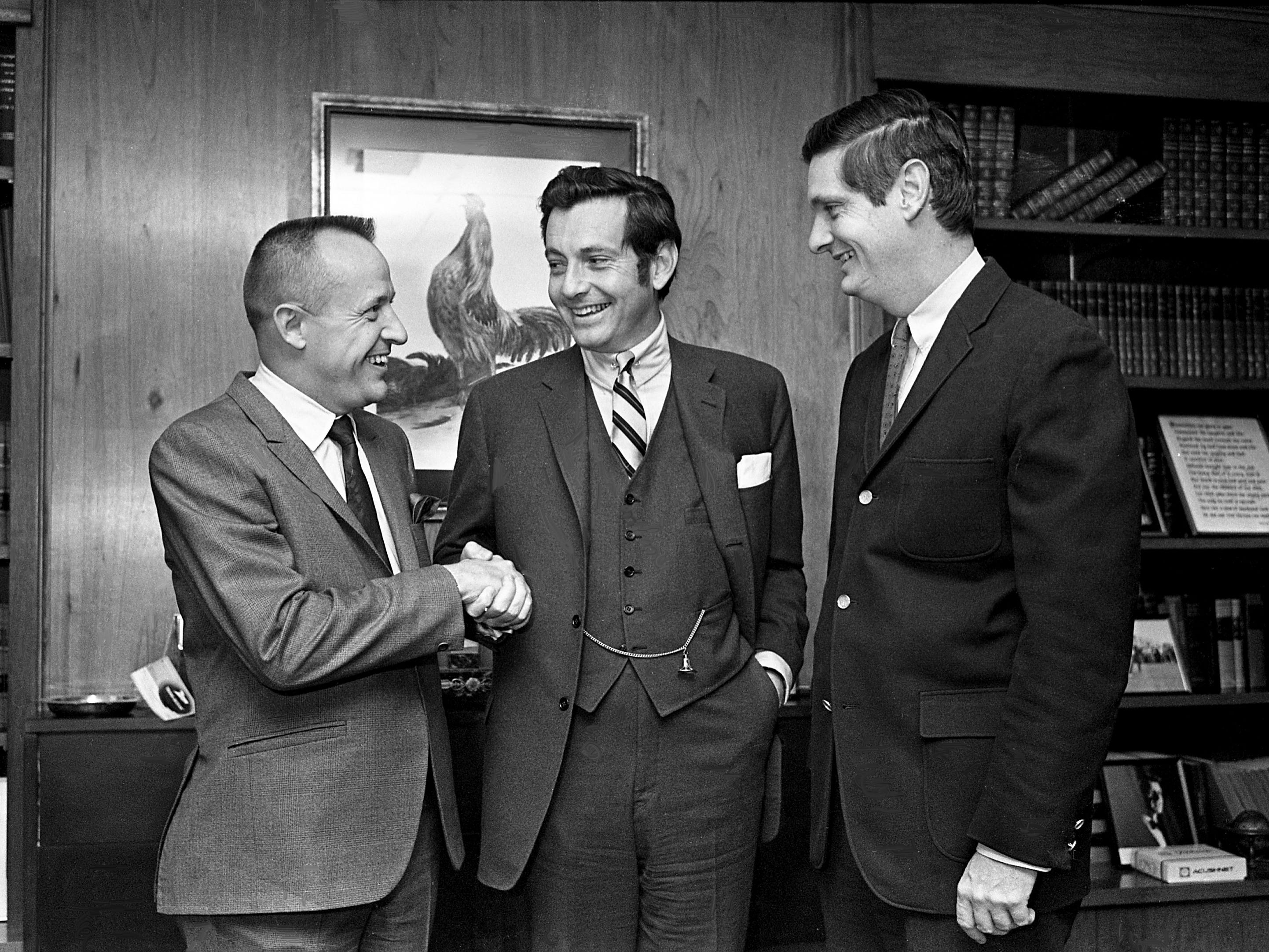 David A. Barrett, left, executive vice president of a newly organized system of child care centers, receives a handshake from John Jay Hooker Jr., president of the firm, as Henry W. Hooker, vice chairman of the board, looks on after the announcement of the still-unnamed company during a news conference Dec. 28, 1968. They say a minimum of 1,000 preschool educational play centers is their goal and the plans for a model center are now being developed.
