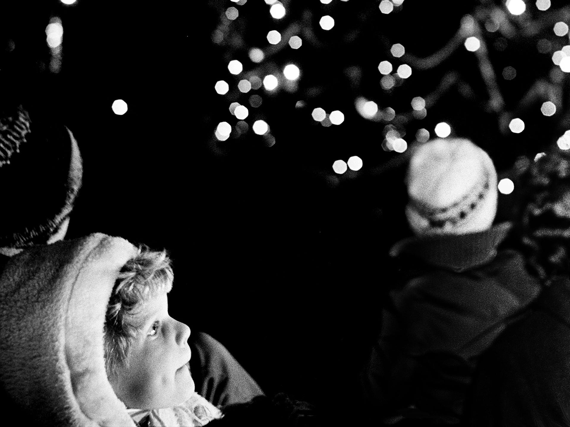 Kristin Swanson, bottom left, 3½, daughter of the Rev. and Mrs. Theodore Swanson, gazes with awe as the light flash on the Metro's Christmas tree on Memorial Square Nov. 26, 1968. More than 2,000 were on hand for the annual Christmas tree lighting ceremony.