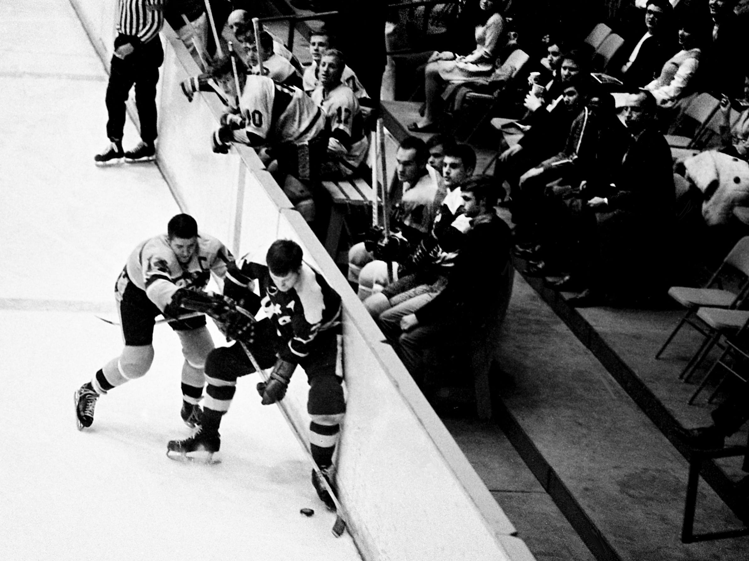With his teammates looking on from the bench, Nashville Dixie Flyers captain Wayne Clairmont (14) goes into the boards to battle Johnstown Jets' Dick Paradise (3) for a loose puck. The Flyers went on to check Johnstown 4-1 before 1,573 fans at Municipal Auditorium on Dec. 15, 1968.