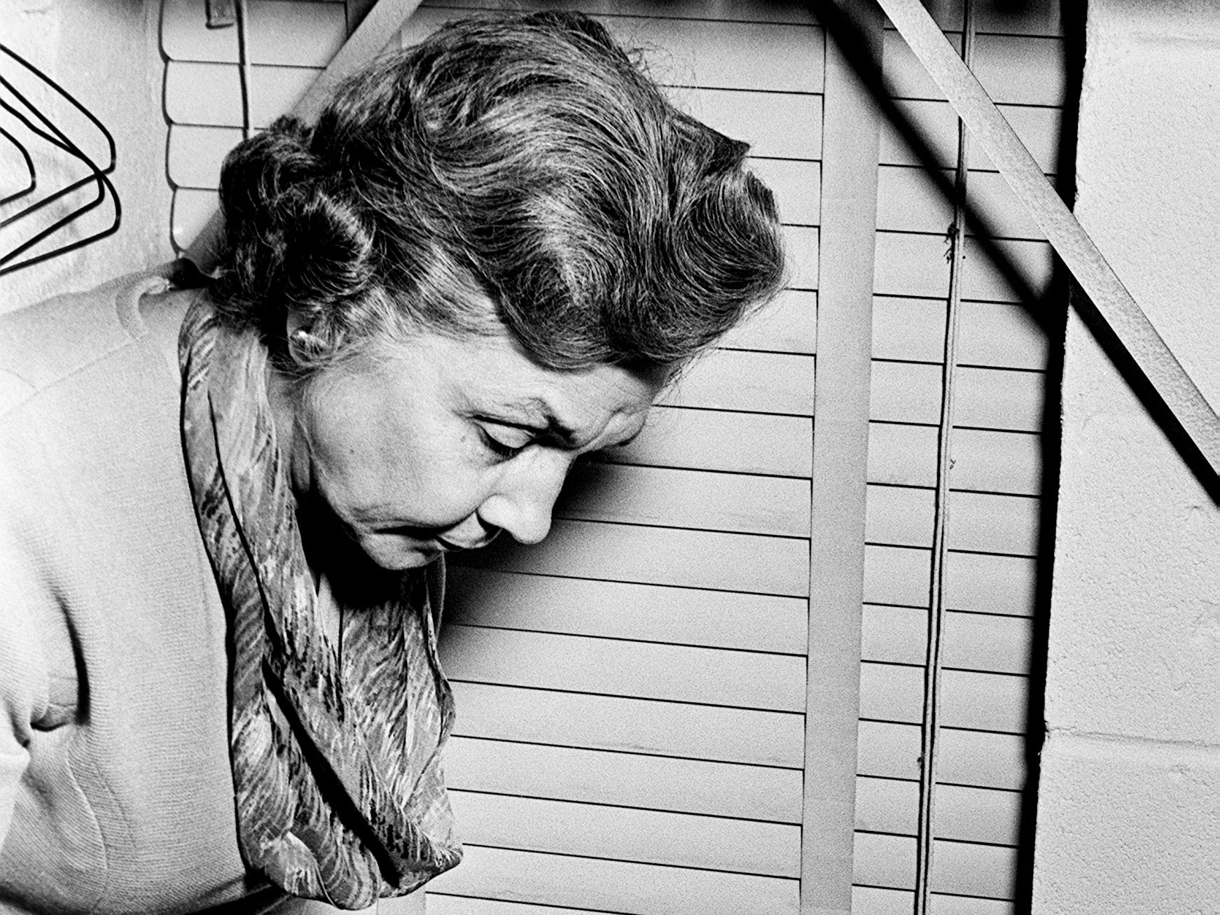 Elise Oliver, director of the State Department of Public Welfare office at 1616 Church St., examines a brick apparently used to break the office window Dec. 2, 1968. They found an empty room once filled with Christmas gifts for children in foster homes.