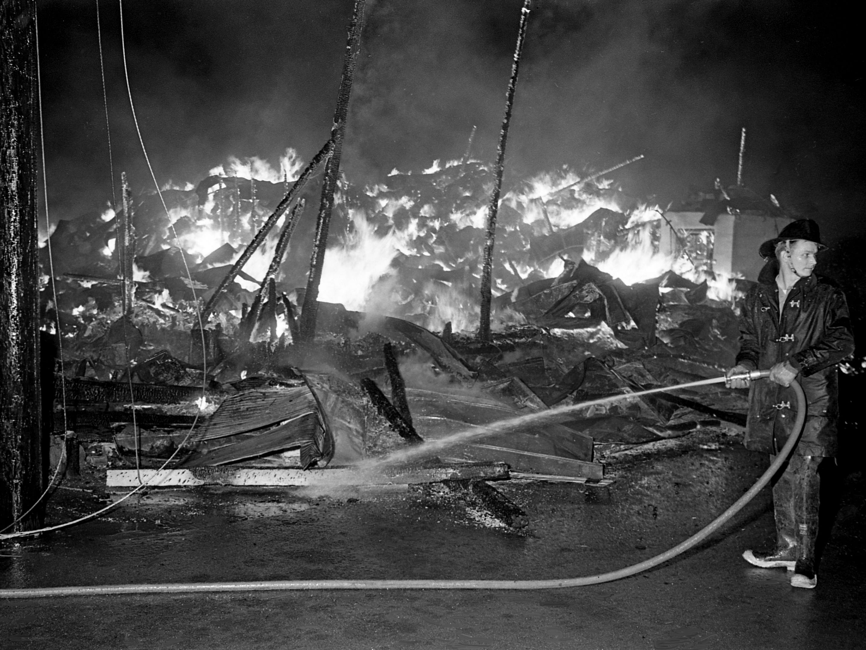 A firefighter works to douse the burning remains of a building Dec. 18, 1968, while others down the street fight to contain the blaze, which destroyed several businesses in Nolensville. Three buildings housing the businesses were burned to the ground, and flames threatened the Harper National Bank and Post Office building for more than an hour.