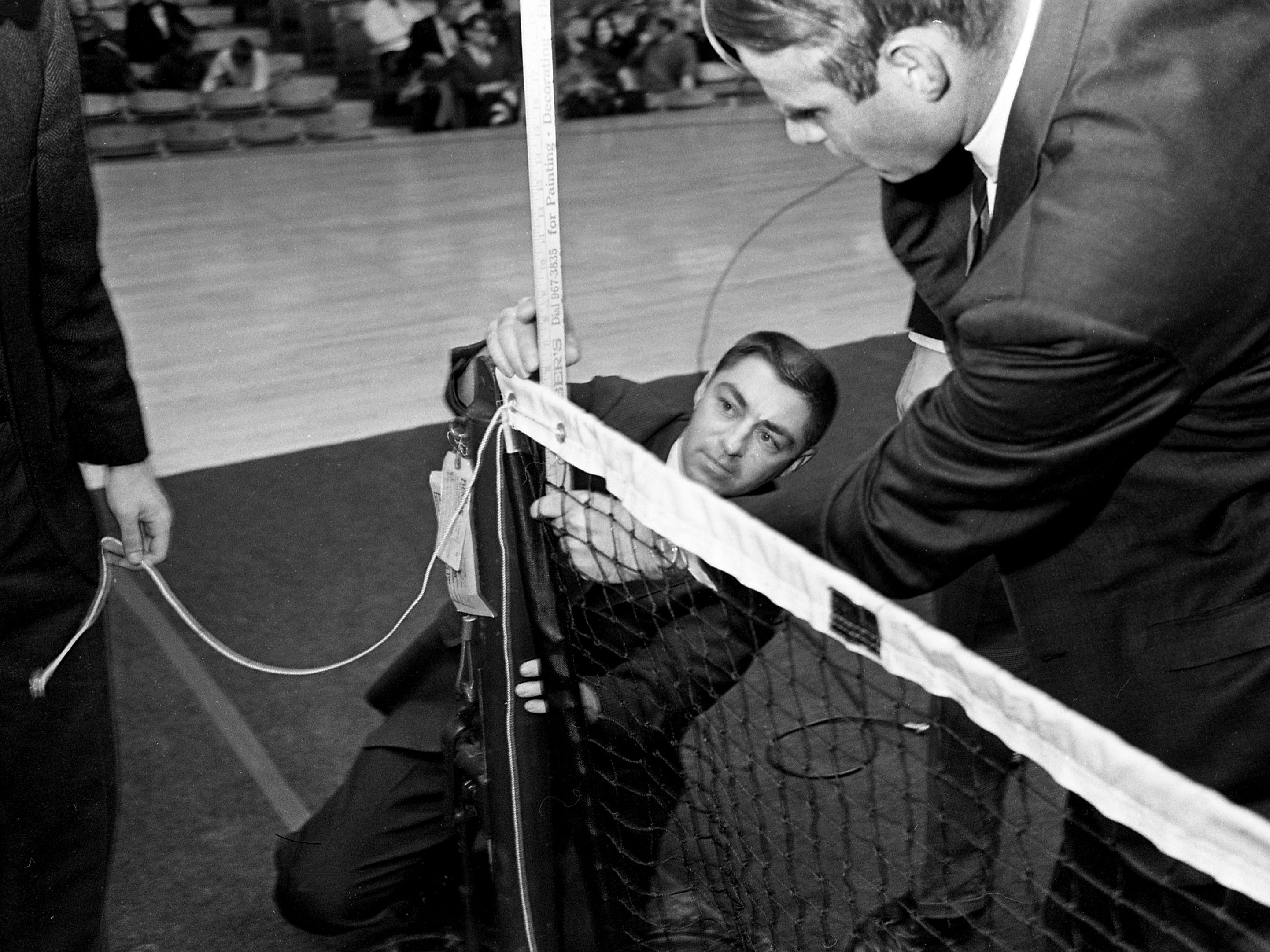Vanderbilt tennis coach Jack Vredevelt, right, and George Baines, who is in charge of Memorial Gym, adjust the net to the proper height before the opening serve of the Dixie Tennis Classic on Dec. 7, 1968.