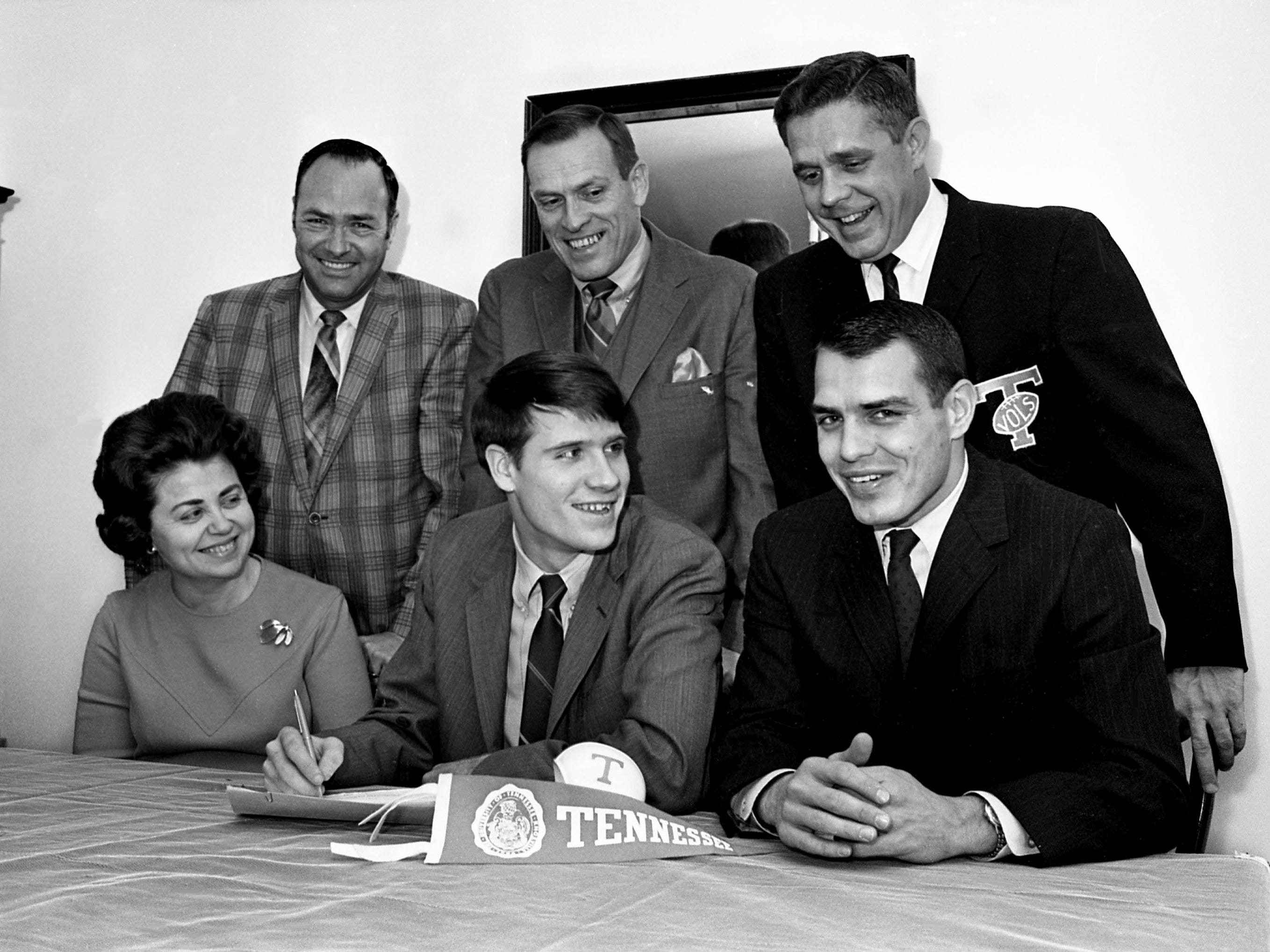 It's Big Orange for Frank Livesay, front center, as the Overton High quarterback signs a grant with the University of Tennessee at 100 Oaks Shopping Center on Dec. 14, 1968. Looking on are his mother, Mrs. Ray Duckworth, seated left, and Vols assistant coach Ken Hatfield, his stepfather, Ray Duckworth, standing left, Overton coach Solon Apple and Vols Nashville recruiter Bill Garrett.