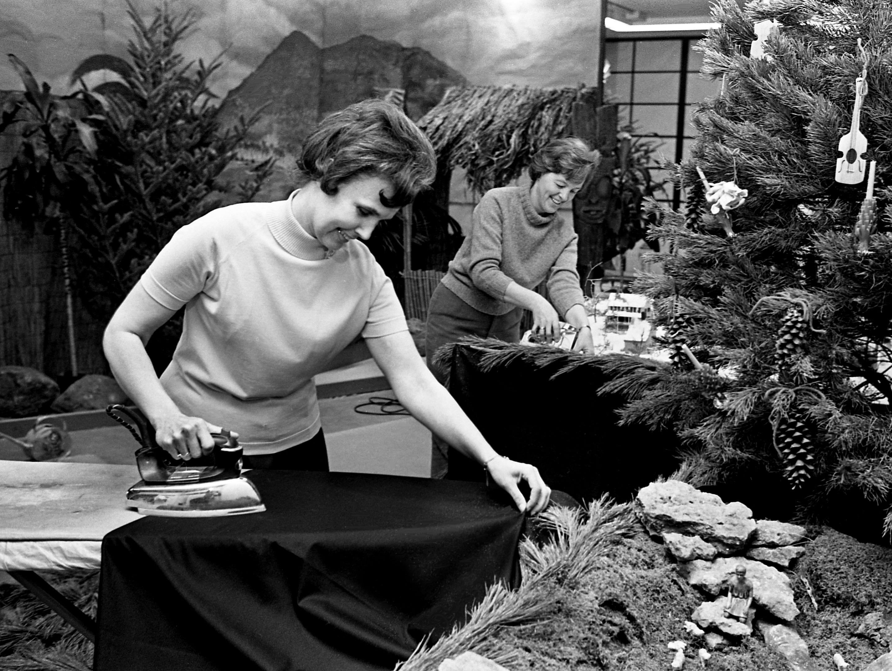 Irons and staplers were busy all week as members of more than 75 garden clubs worked on the 21 trees from many lands and seven exhibits for the upcoming fourth annual Christmas at Cheekwood event. Ironing material for the skirts of the Fleur de Lis Garden Club exhibit Dec. 3, 1968, is Mrs. Lem Tanksley, left, and stapling is Mrs. O.D. Glaus.