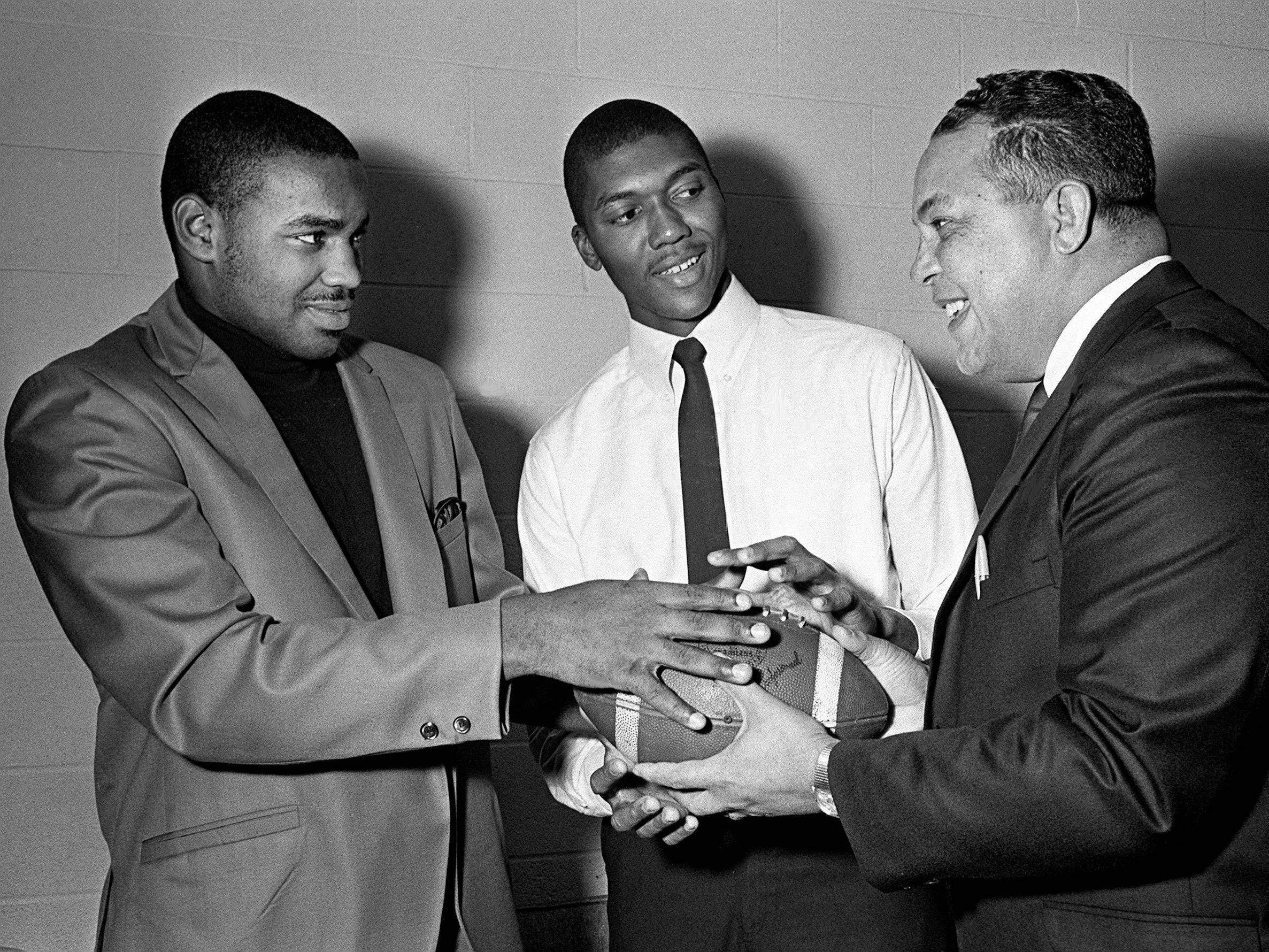 Tennessee A&I State coach John Merritt, right, hands off to a pair of his newest signees, Cameron High stars Shawney Wynn, left, and Aaron Bostick, on Dec. 16, 1968.