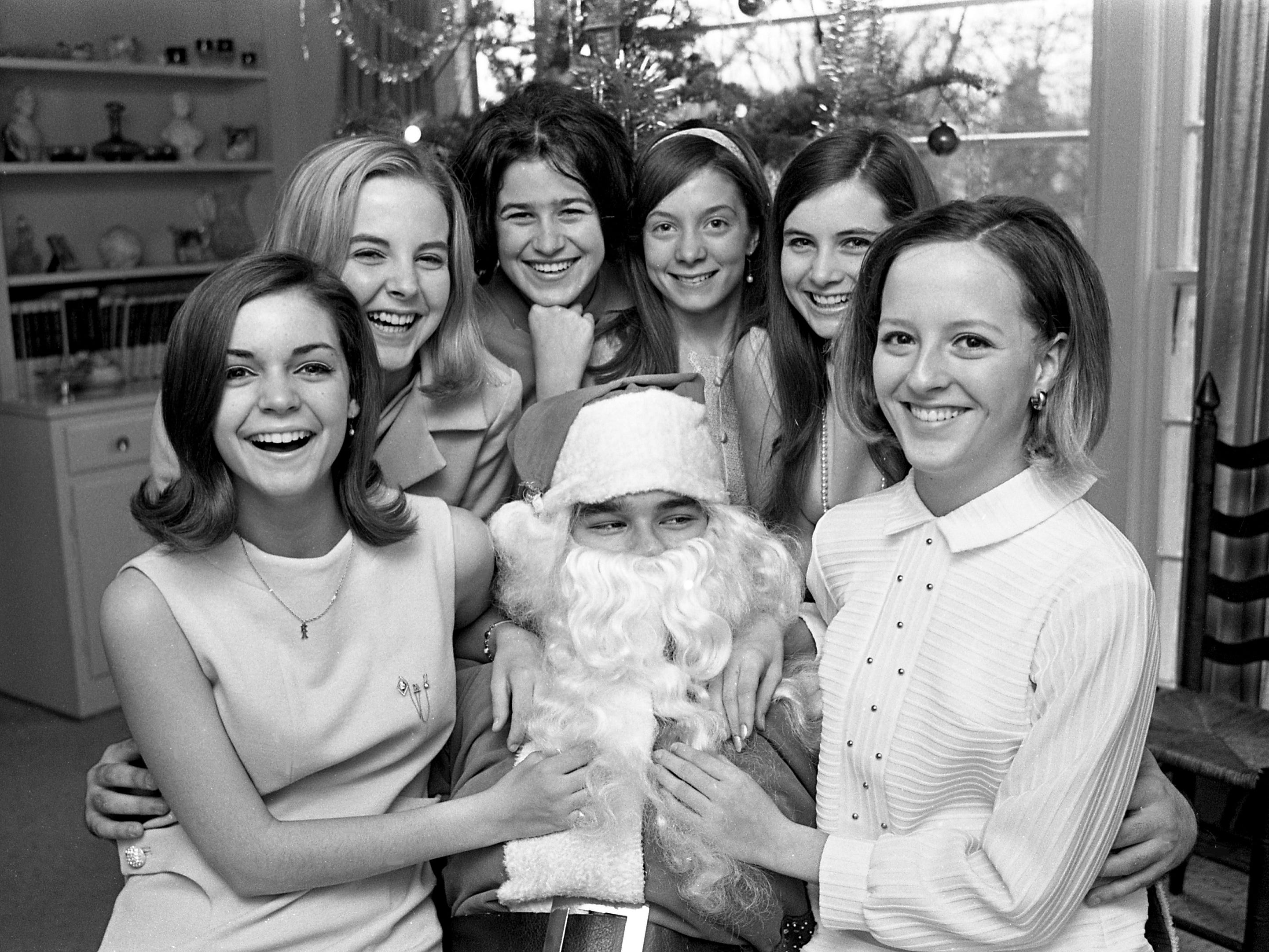 Members of Delta Gamma Beta Sorority entertained Dec. 22, 1968 at a holiday party in honor of their rushes and their mothers at the home of Mrs. Sydney Spellings on West Meade Drive. Giving Santa, played by Mike Kimbrough, a big hug are Miss Ann Melcher, left, Miss Brooks Baker, Miss Suzanne Collier, Miss Debbie Caddington, Miss Debbie Dale and Miss Sydney Spellings.