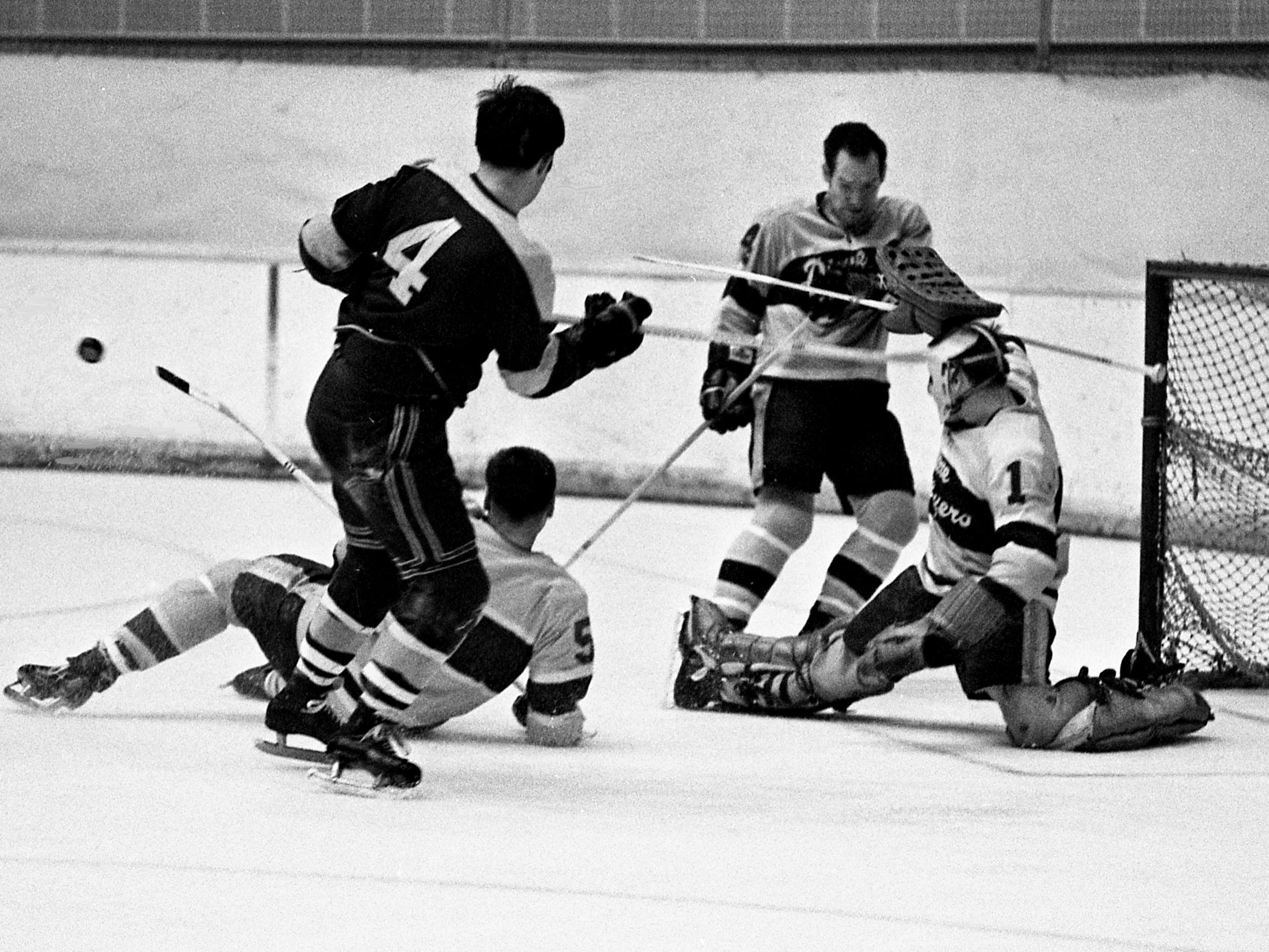 With teammates Leo Olivier (5) and Flo Pilote, second from right, aiding, Nashville Dixie Flyers goalie Duffy Lewis (1) slaps away the puck from a New Haven Blades shooter as Bill Orr (4) of the Blades moved in for a chance at a rebound. The Flyers rolled to a 7-3 victory before a crowd of 1,873 at Municipal Auditorium on Dec. 12, 1968.