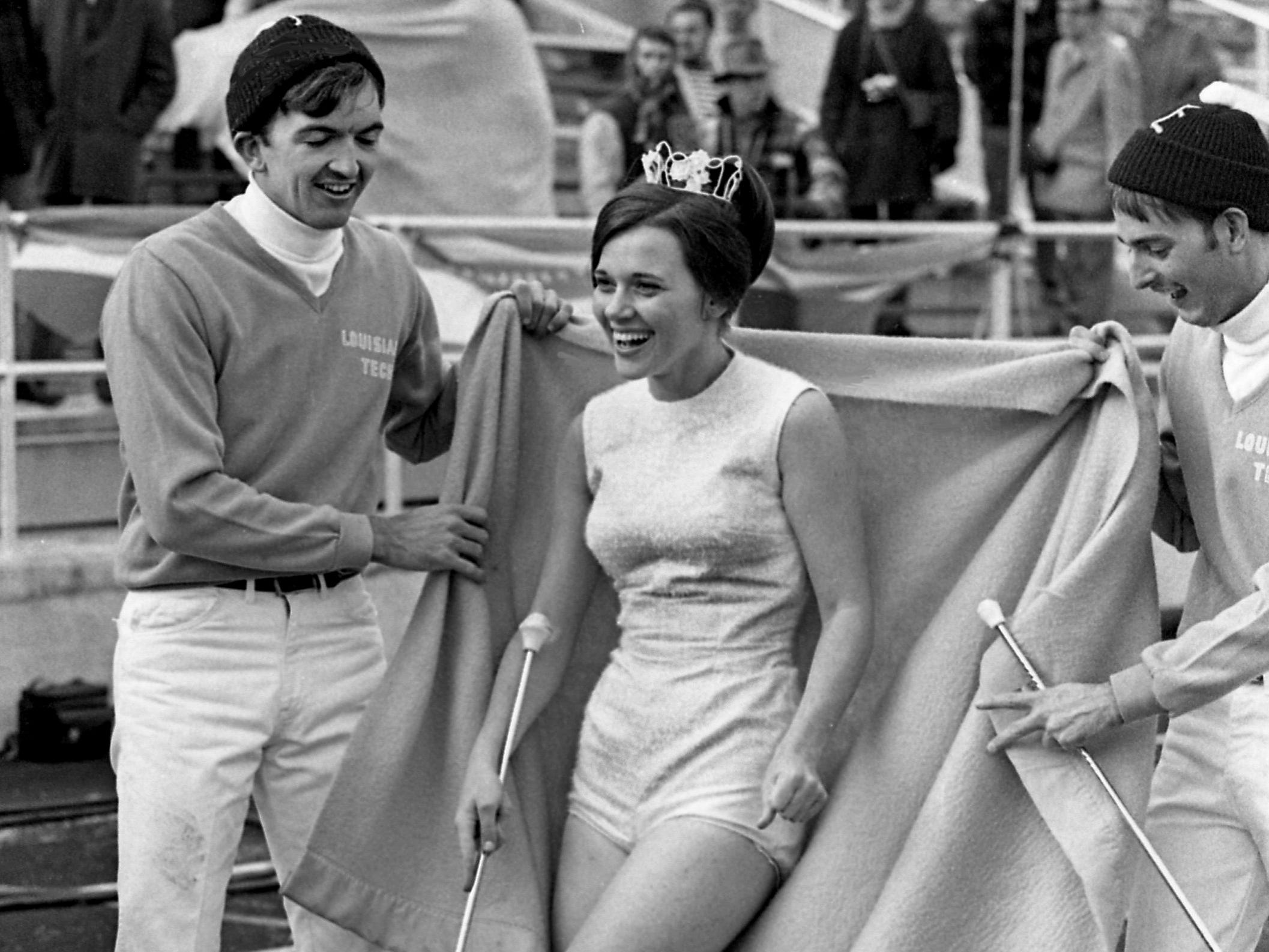 Louisiana Tech majorette Cenelle Callais, center, comes out from under her blanket with help from cheerleaders Tommy Davis and Ernest Wadlington for the halftime show during the fifth annual Grantland Rice Bowl at Middle Tennessee State University on Dec. 14, 1968.