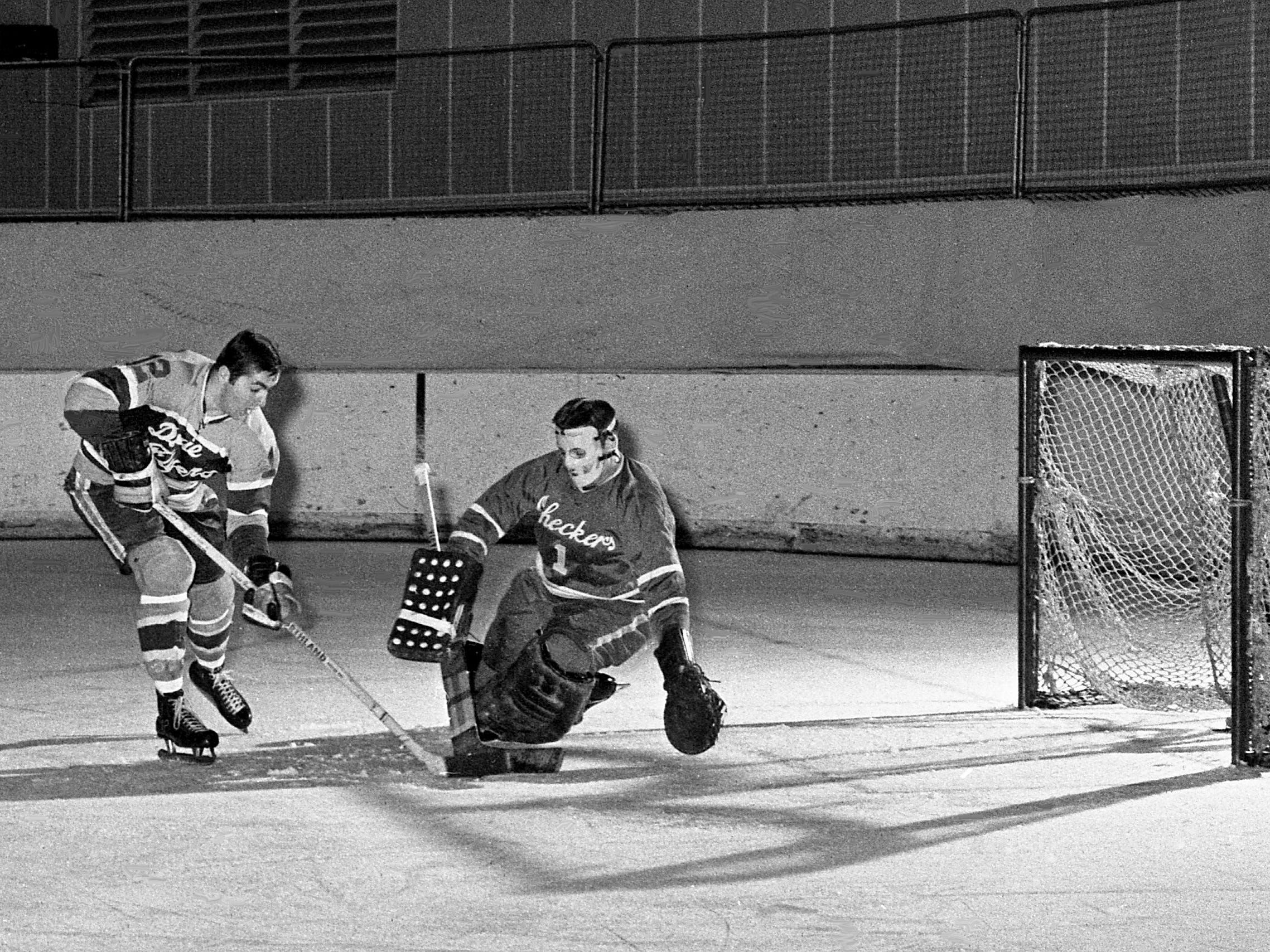 Nashville Dixie Flyers center Neil Clairmont (12) makes a move on Charlotte Checkers goalie Bob Whidden as the Flyers breezed to an 8-1 victory at Municipal Auditorium on Dec. 17, 1968.