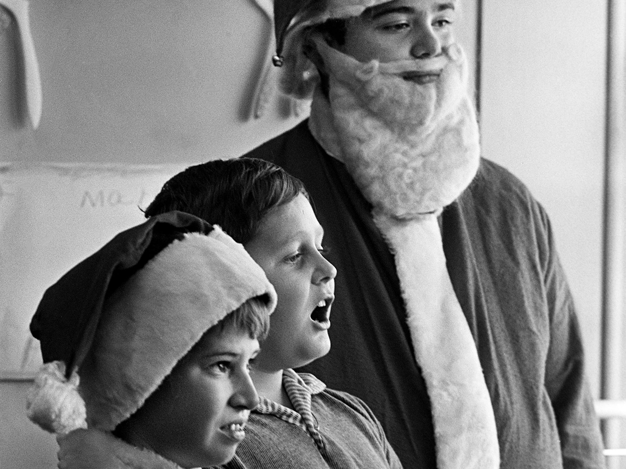 """Students Barry Eubanks, left, 11, Robert Stevens, 10, and Mike Baggett, 13, in special education classes at Jere Baxter Elementary School act out a scene from their Christmas play, """"The Real Santa Claus,"""" Dec. 19, 1968."""