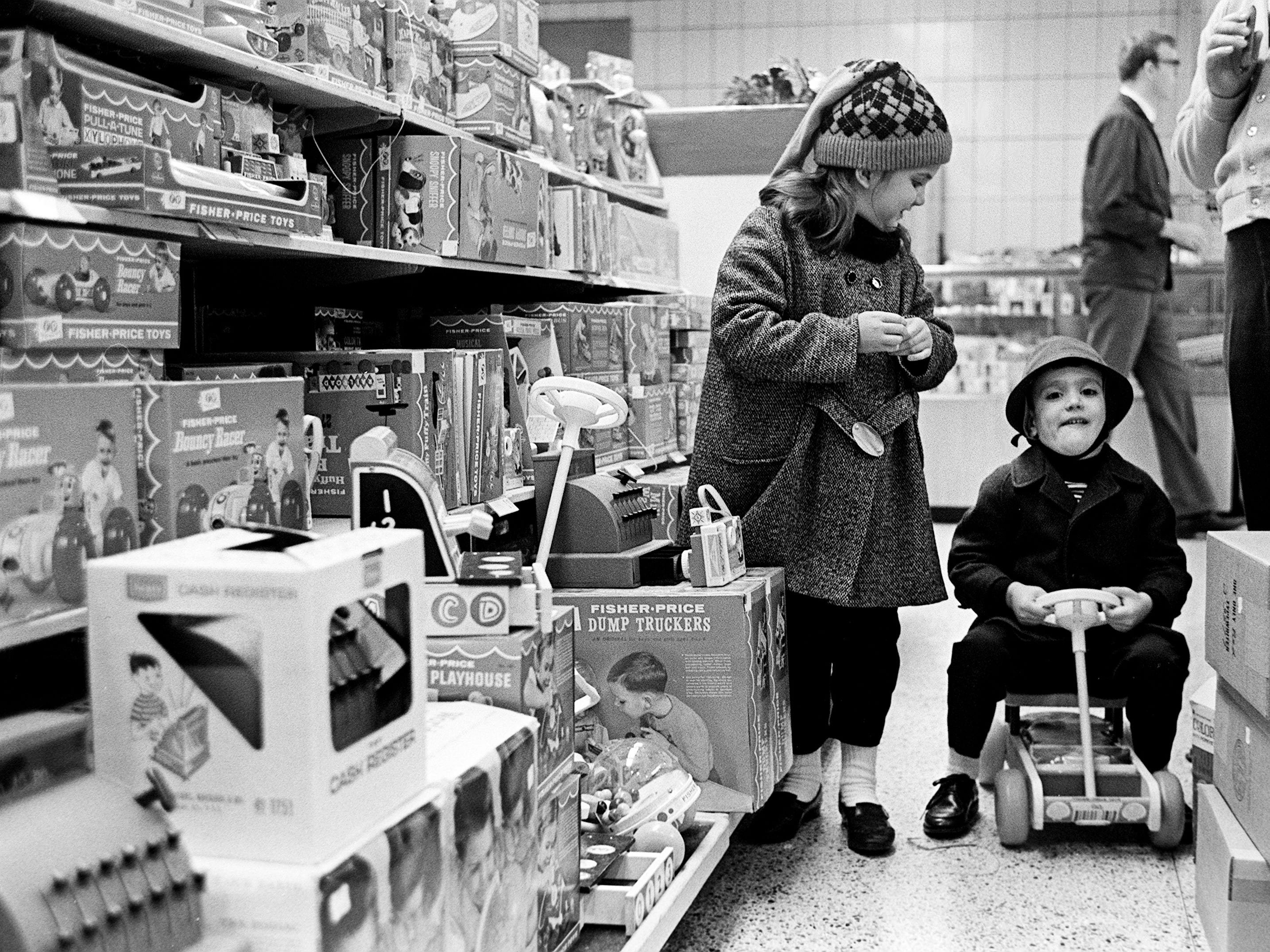 Sherry Spray, left, 6, watches her brother Jerry, 1, try out one of the many Christmas toys Santa might have in his sleight this year at a downtown Nashville department store Dec. 12, 1968.
