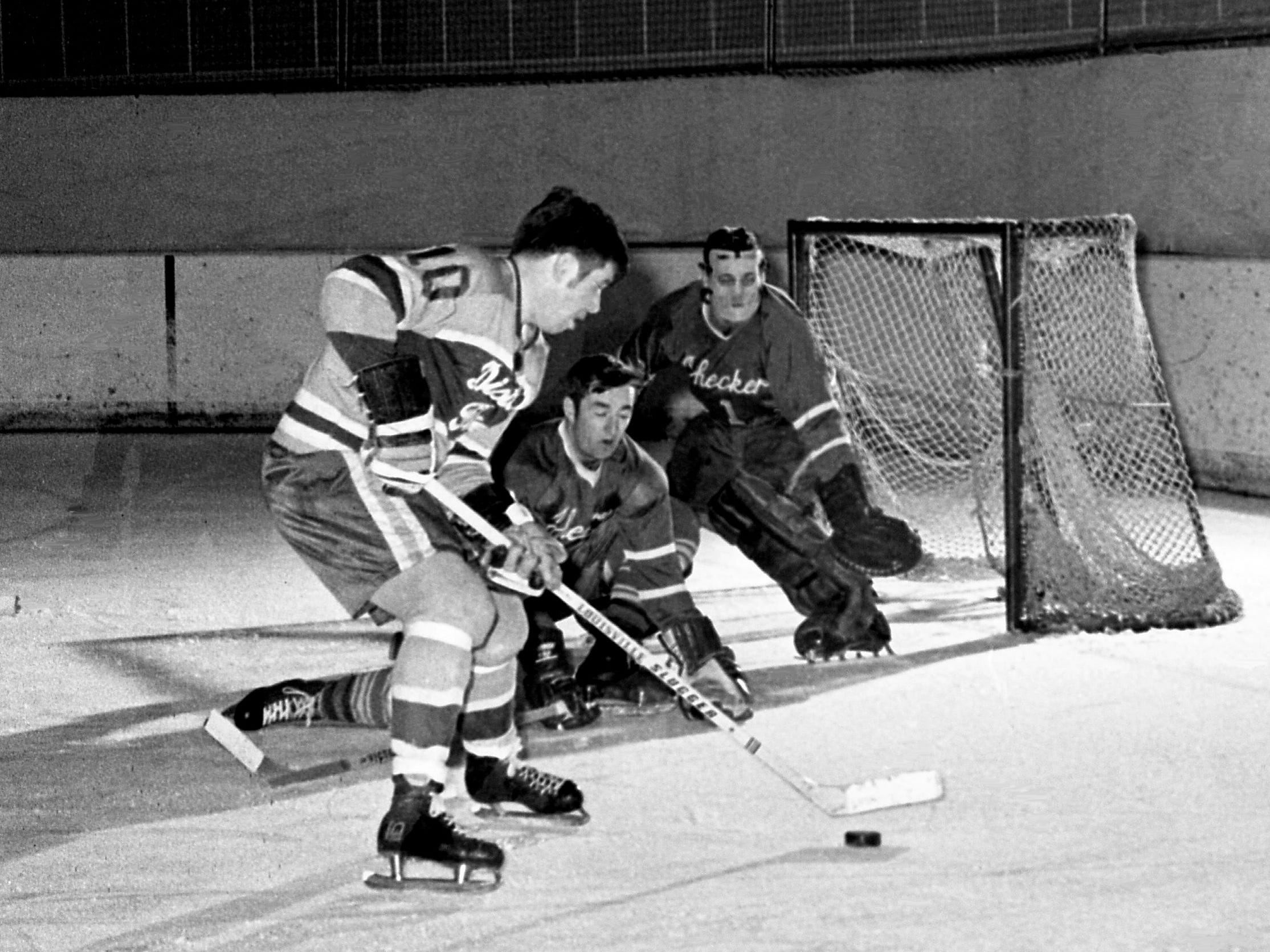 Despite the effort of Charlotte Checkers defenseman Frank Golembrosky, center, and goalie Bob Whidden, Nashville Dixie Flyers winger Andre Lajeunesse (10) is ready to score the first goal for the Flyers in their 8-1 victory at Municipal Auditorium on Dec. 17, 1968.