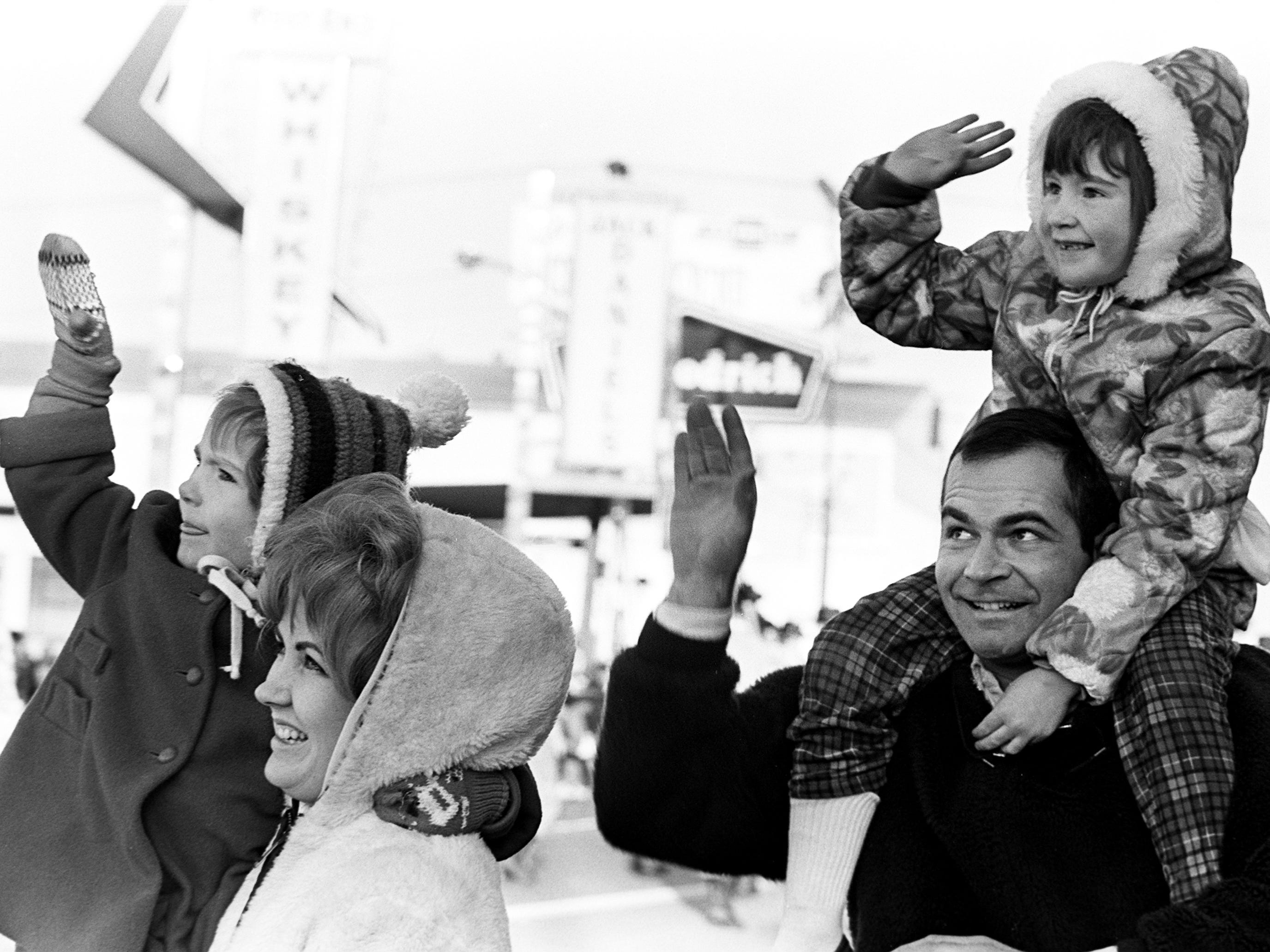 Dana Hight, 4, left, and Deannie Hight, 6, right, got a lift to see and wave to Santa from their parents, Mr. and Mrs. D.W. Hight of Matthew Ave. during the 16th annual Nashville Christmas parade Dec. 8, 1968.