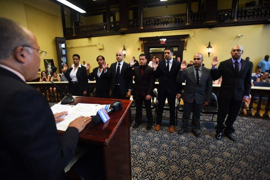 Roger Then, second from right, is sworn in as a Paterson police officer along with six other recruits in 2016.