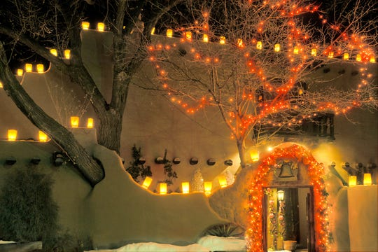 Farolitos along Canyon Road in Santa Fe invite visitors on Christmas Eve to enjoy the decorations along with a treat of chocolate or cider.