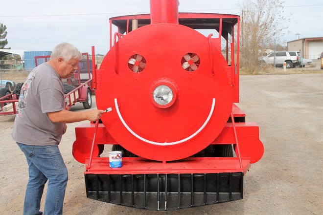 Alamogordo Toys for Tots Coordinator Wally Anderson spruces up a donated train for Saturday's Parade of Lights.