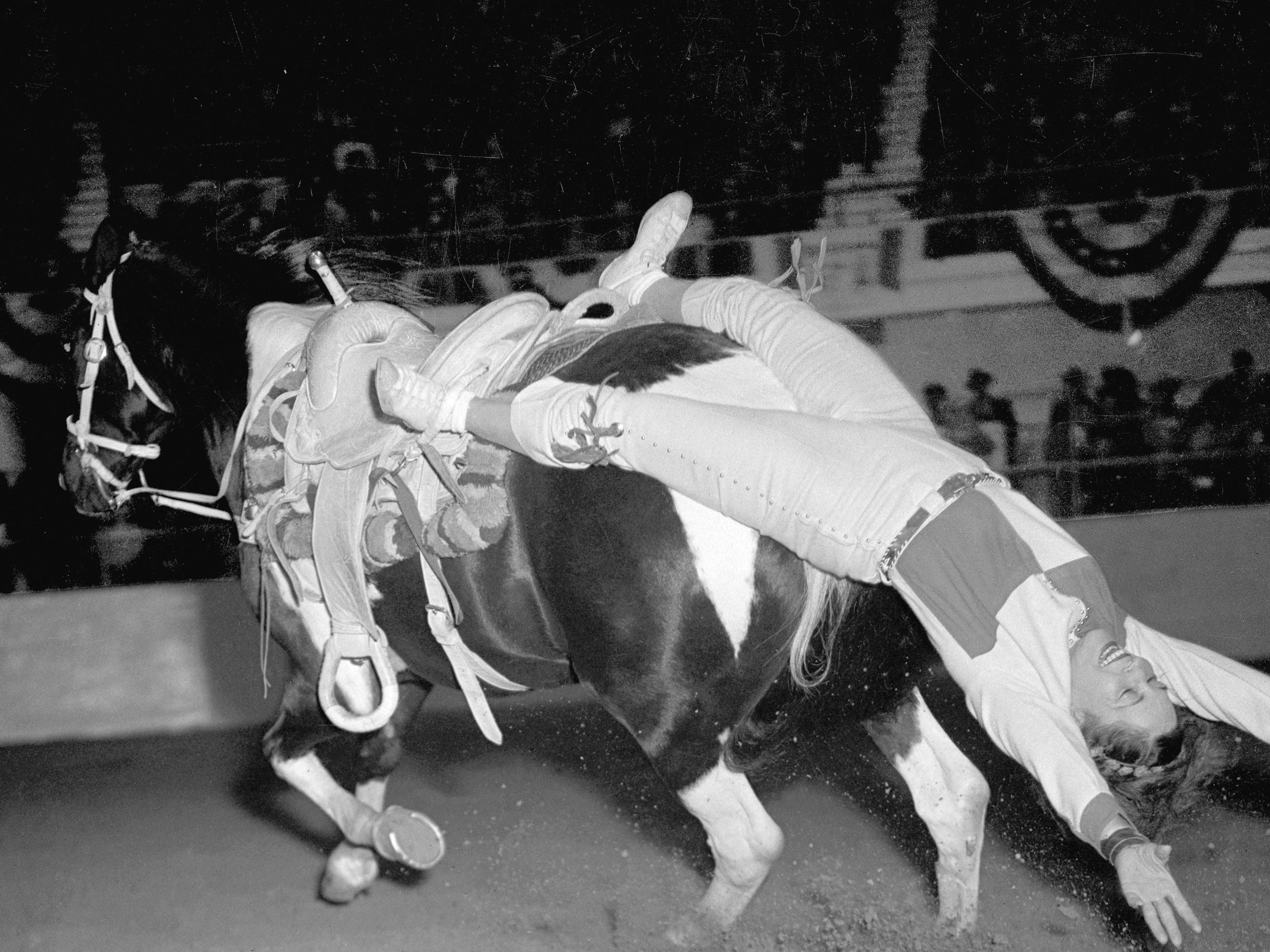 A cowgirl displays her trick riding abilities during Girls Rodeo Association rodeo in the 1940s.