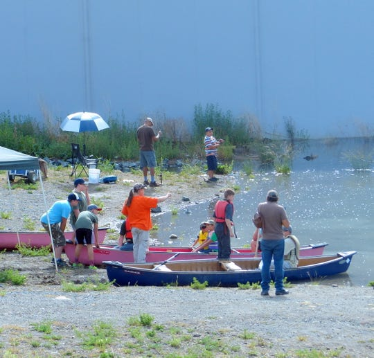 During a recent youth fishing day, young anglers were taken on canoe rides on the lake. The lake level has risen significantly since this event as the village refills after installing a liner to reduce leakage.