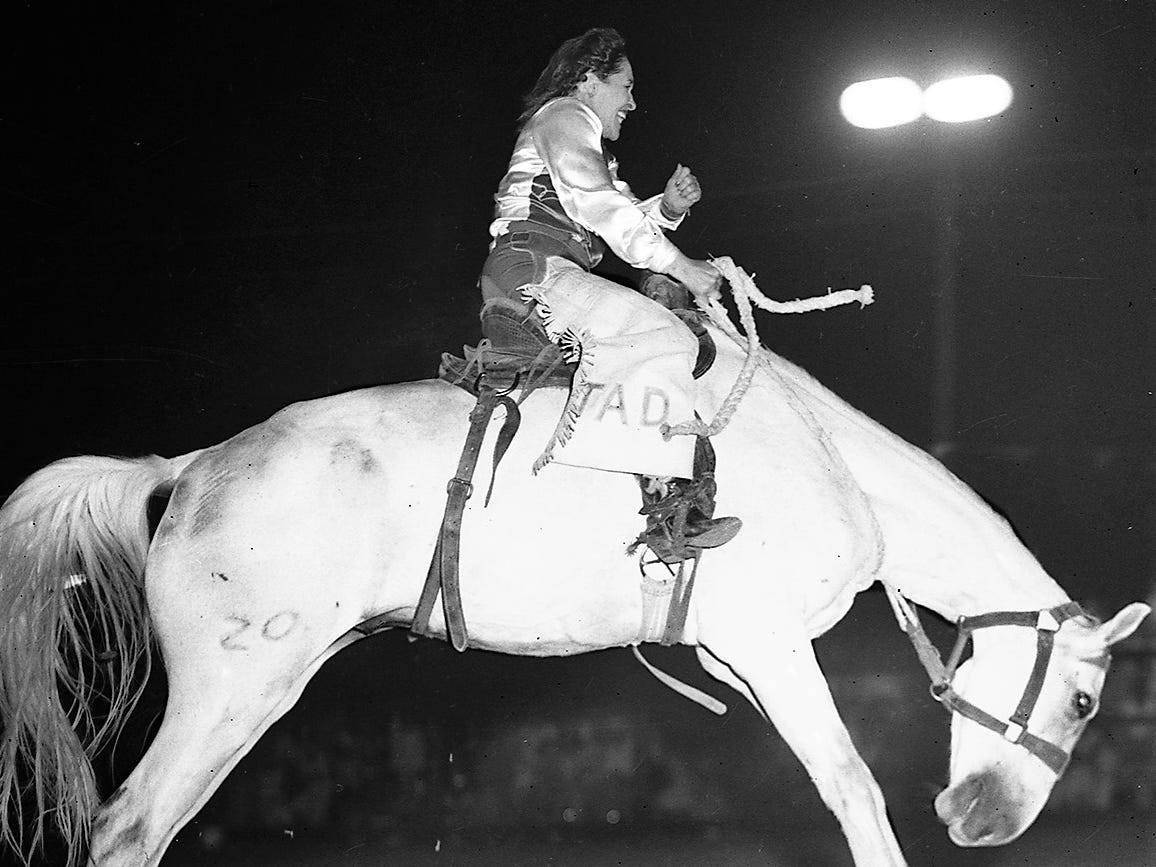 A cowgirl competes in a 1940s Girls Rodeo Association bronco busting competition.