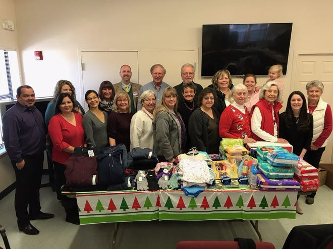 Some of the members of the Lincoln County Community Health Committee assembled at the table full of items donated to local students and foster children.