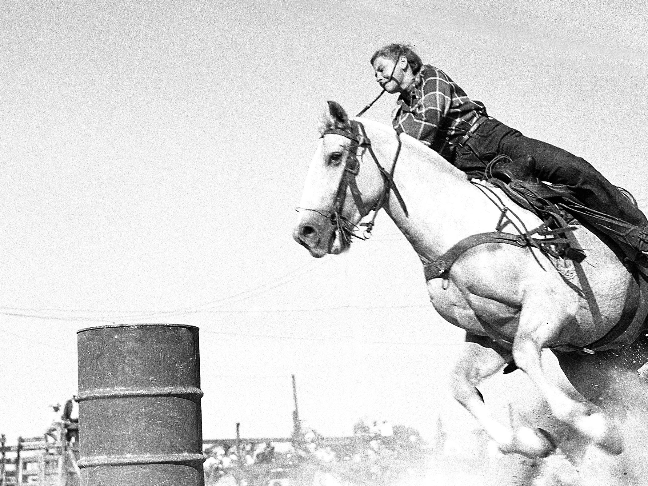 A cowgirl competes in a Girls Rodeo Association barrel racing competition in the 1940s.