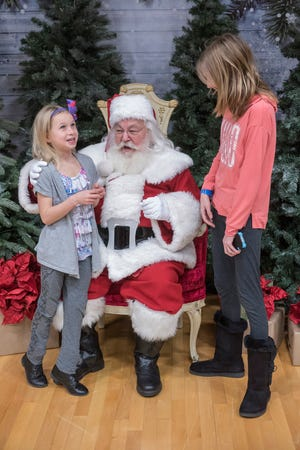 Sisters Cadence Swickard, 8 years old, and Brianna Swickard, 13 years old, spend a little time with Santa Claus.
