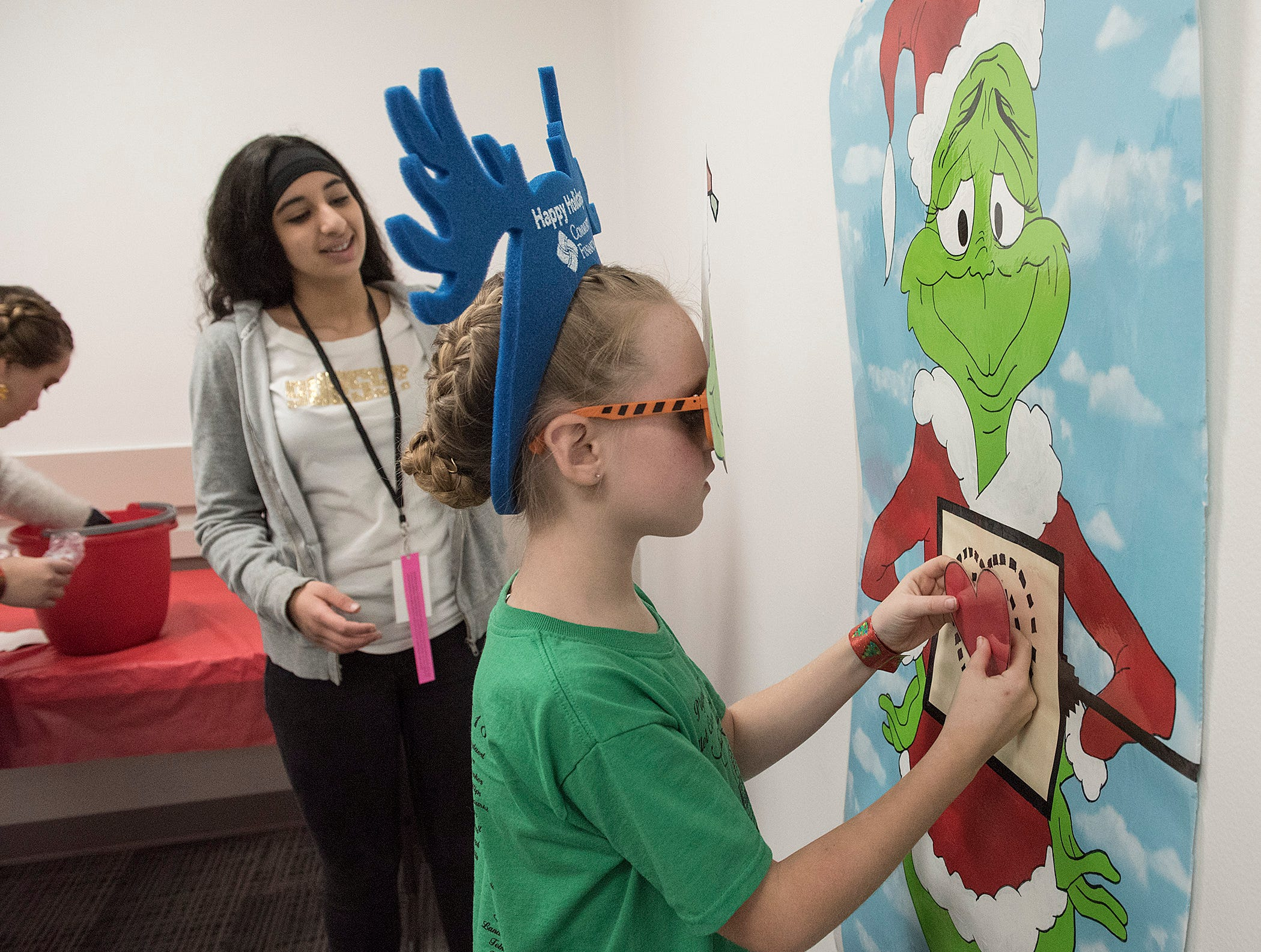 In the Goodfellows game room, 9 year old Marina Miekstyn places the heart in just the right place on the Grinch. Volunteer Shereen Alyasiry gives encouragement.