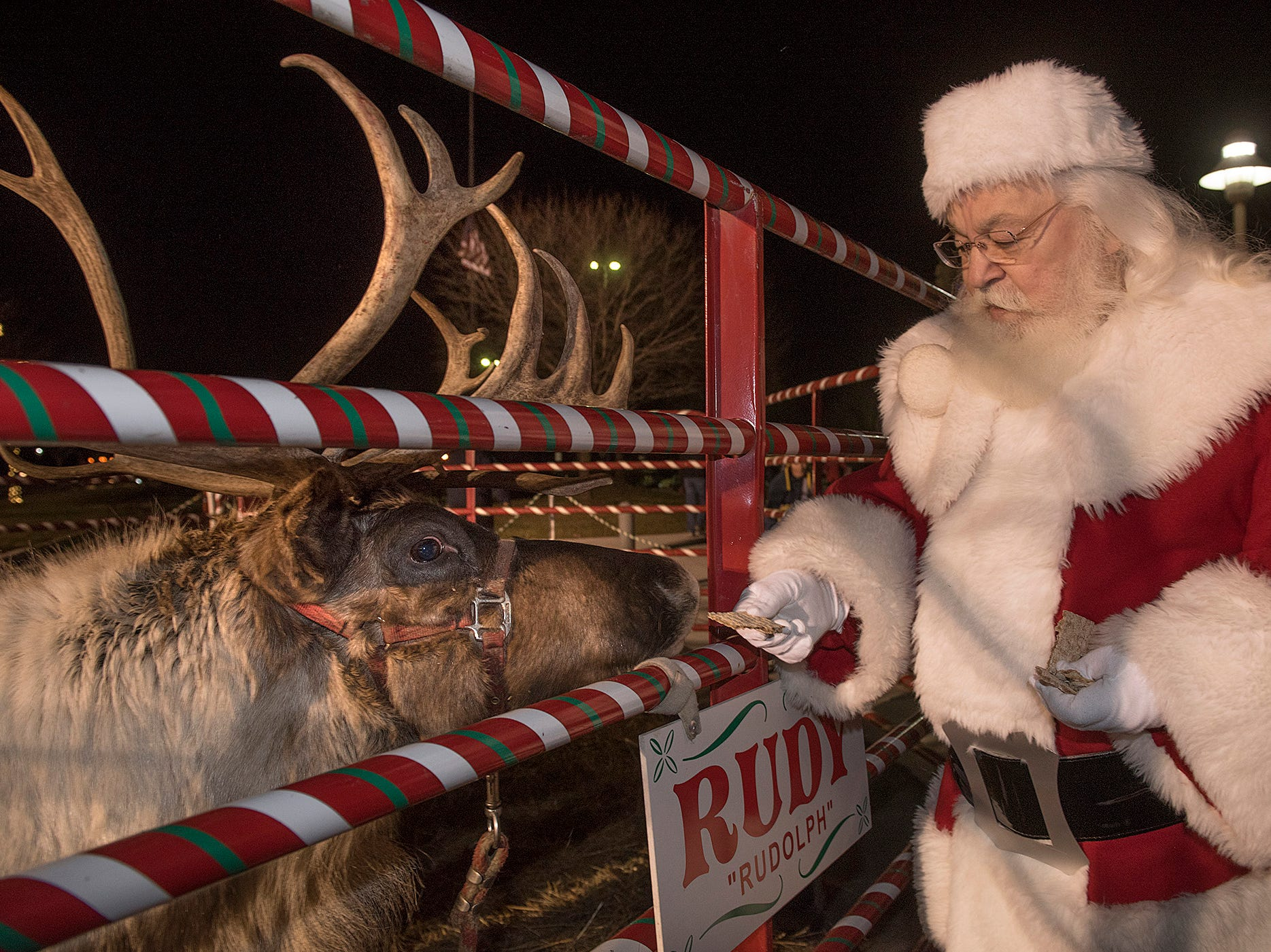 Santa takes a break to feed Rudolph.
