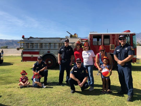 Touch-A-Truck participants Fletcher Mansell (4) and Camden Pierce (3) met firefighters Christopher Pruckler, Virgil Messer, Zac Alfaro and Nestor Zelaya from Cal-Fire/Riverside County Fire Department, north Rancho Mirage Station, 69 House, which is located next door to CDMOD, along with CDMOD Development Coordinator Victoria Volsky and CEO Carol Scott.