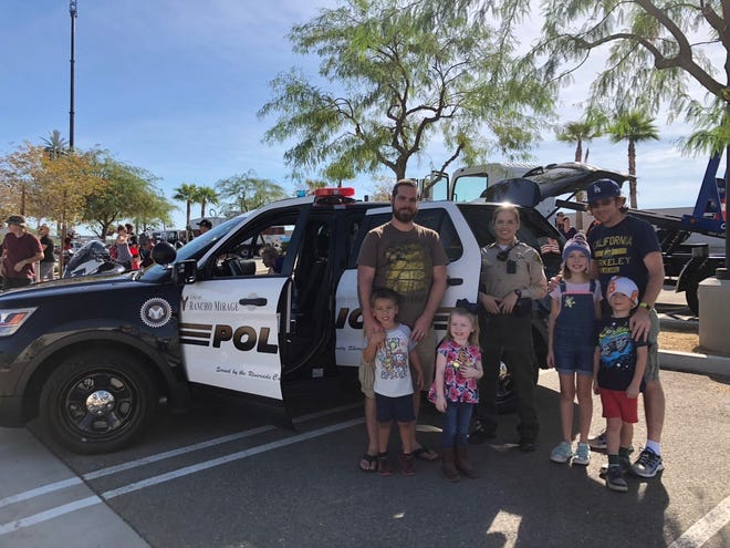 After exploring the inside of a City of Rancho Mirage police unit, Sean Miller, Asher Miller (4), Ryliegh Offerdahl (2), Nathan Taylor, Maggie Taylor (9) and Ben Taylor (5) pose with Deputy Jennifer Benoit from the Riverside County Sheriff's Department, which serves as the City of Rancho Mirage's Police Department.