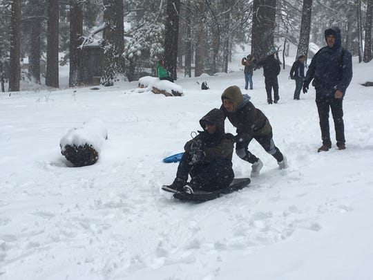 Desert Hot Springs resident Jesus Suarez pushes his brother, Jose, on a sled near the Palm Springs Aerial Tramway's mountain station Thursday. People played in snow that fell overnight on the San Jacinto Mountains.