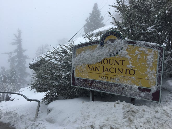 A sign is covered in snow near the Palm Springs Aerial Tramway's mountain station following a storm in early December. This week, the Coachella Valley is under a freeze warning due to temperatures that could drop to 26 degrees.