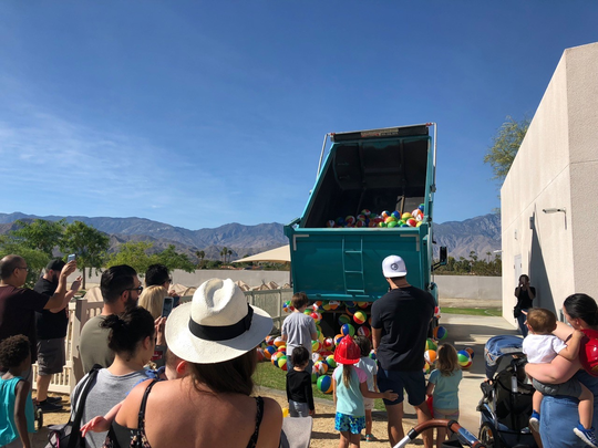 Visitors to CDMOD's Touch-A-Truck event watched up close as a dump truck from West Coast Sand and Gravel dumped inflatable balls at their feet.