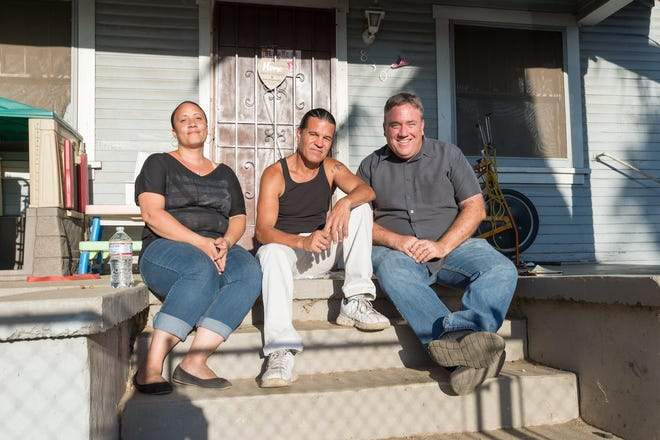 Current tenants Destiny Moore Hernandez and her husband Louis Hernandez, along with author Joe Mathews, are pictured on the front steps of 830 Ohio in September.