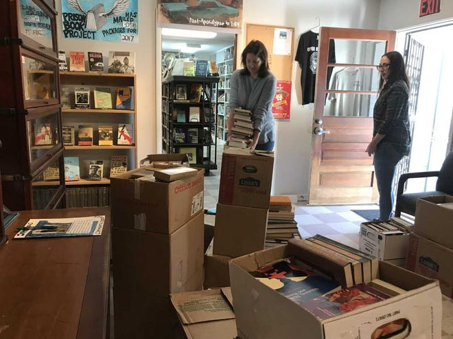 UWF history professor Amy Mitchell-Cook carries boxes of books into Open Books, while Open Books volunteer Rebecca Carlson gets ready to head outside to load more boxes. UWF donated an estimated 1,000 books to the non-profit Open Books.