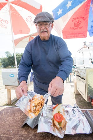 Owner Ray Gluszek completes an order of a chili cheese dog and a a Chicago Style dog at his RG's Cafe hot dog stand on Barrancas Avenue in Warrington on Thursday, December 6, 2018.